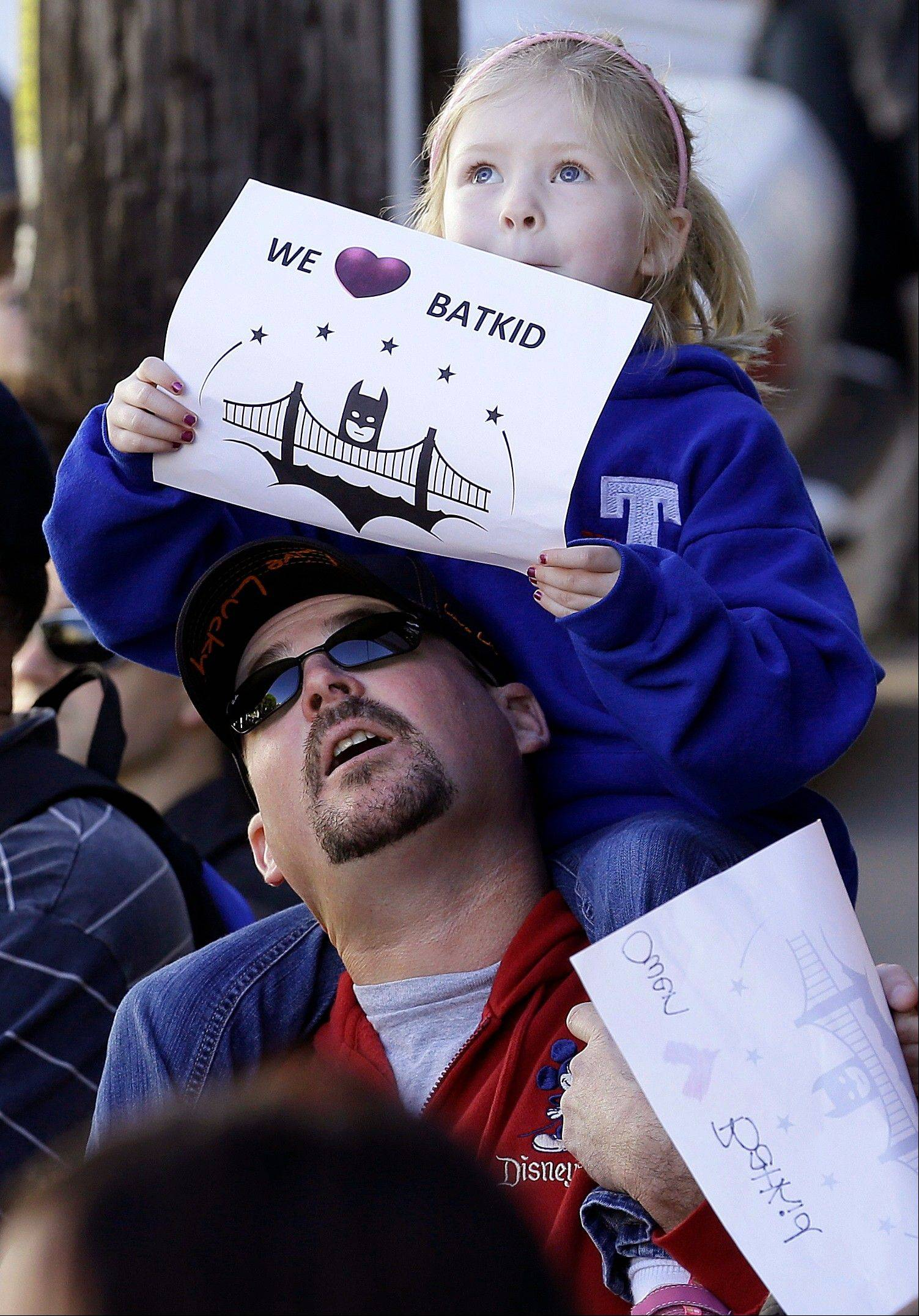 "Daniel Fry holds up his daughter Kayla, 5, as they wait for Miles Scott, dressed as Batkid, in San Francisco, Friday, Nov. 15, 2013. San Francisco turned into Gotham City on Friday, as city officials helped fulfill Scott's wish to be ""Batkid.""�Scott, a leukemia patient from Tulelake in far Northern California, was called into service on Friday morning by San Francisco Police Chief Greg Suhr to help fight crime, The Greater Bay Area Make-A-Wish Foundation says."