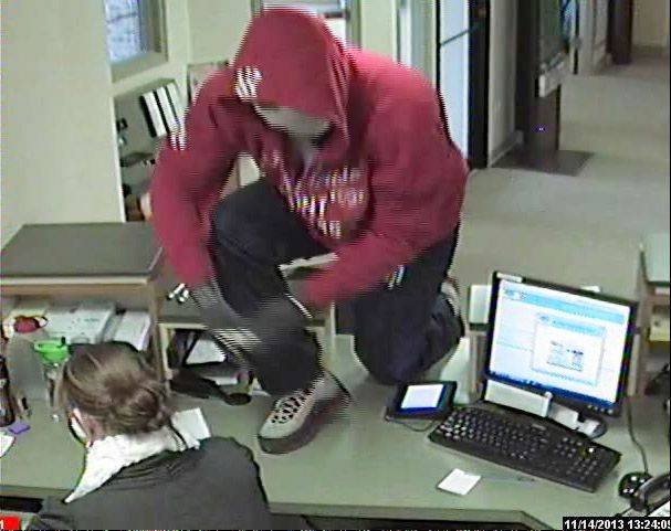 Security video shows the suspect in Thursday's robbery of the Community Trust Credit Union in Gurnee as he jumps on the counter.