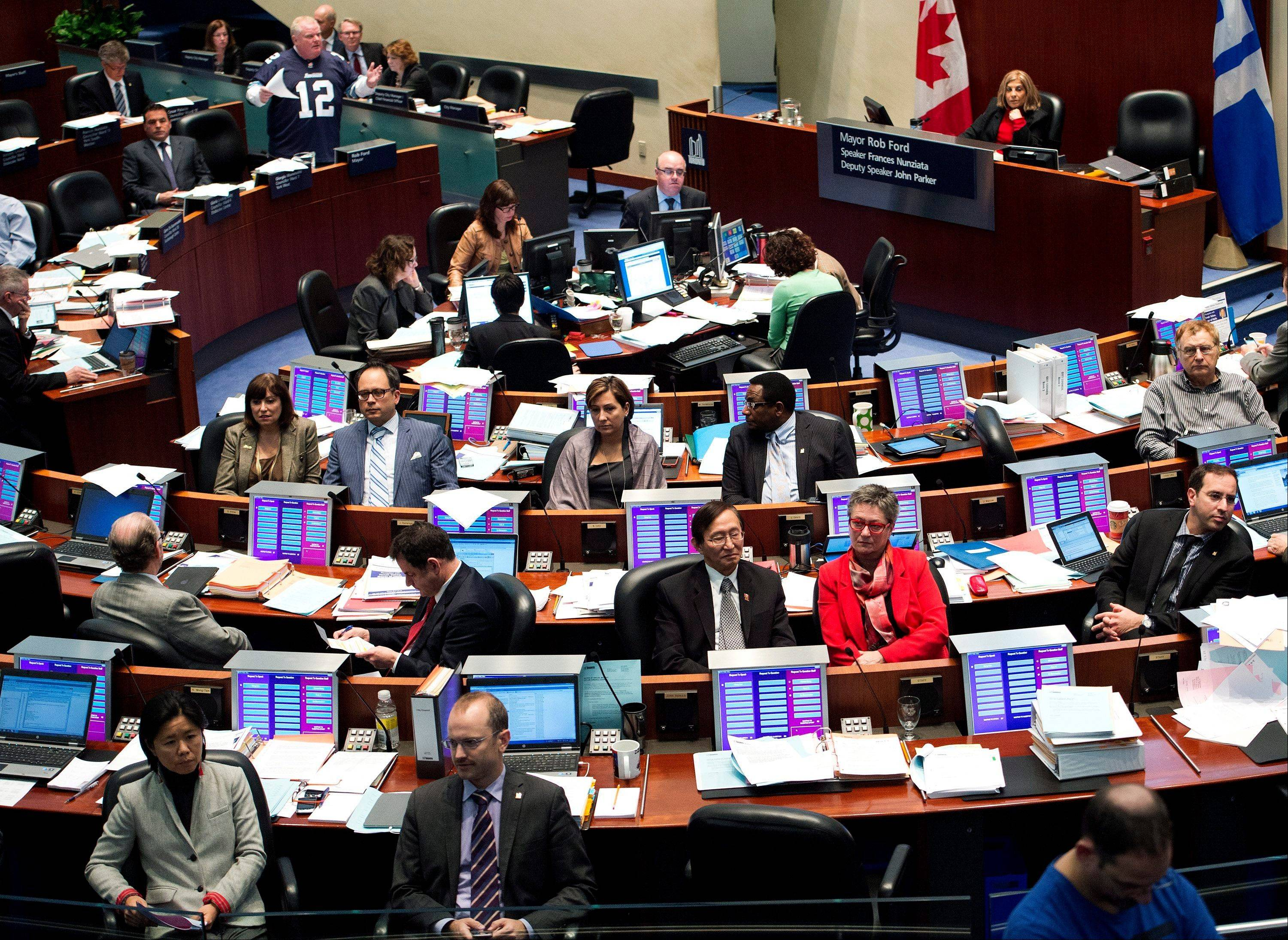 City Council members turn their backs in protest as Toronto Mayor Rob Ford, standing top left, addresses the council during a session at City Hall in Toronto on Thursday, Nov. 14, 2013.