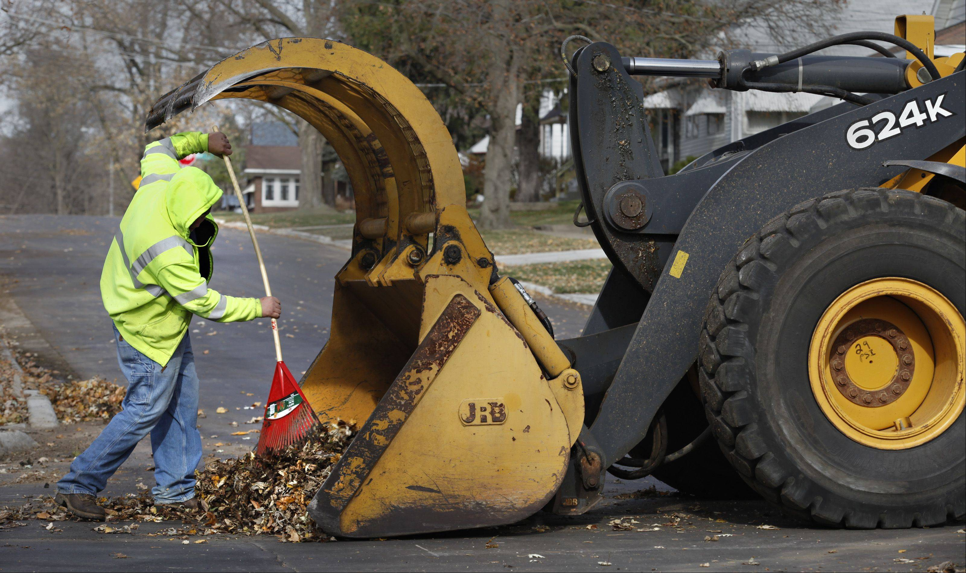 Elgin Public Works employee Chris Becker takes advantage of decent weather Thursday to clean up leaves in the city.