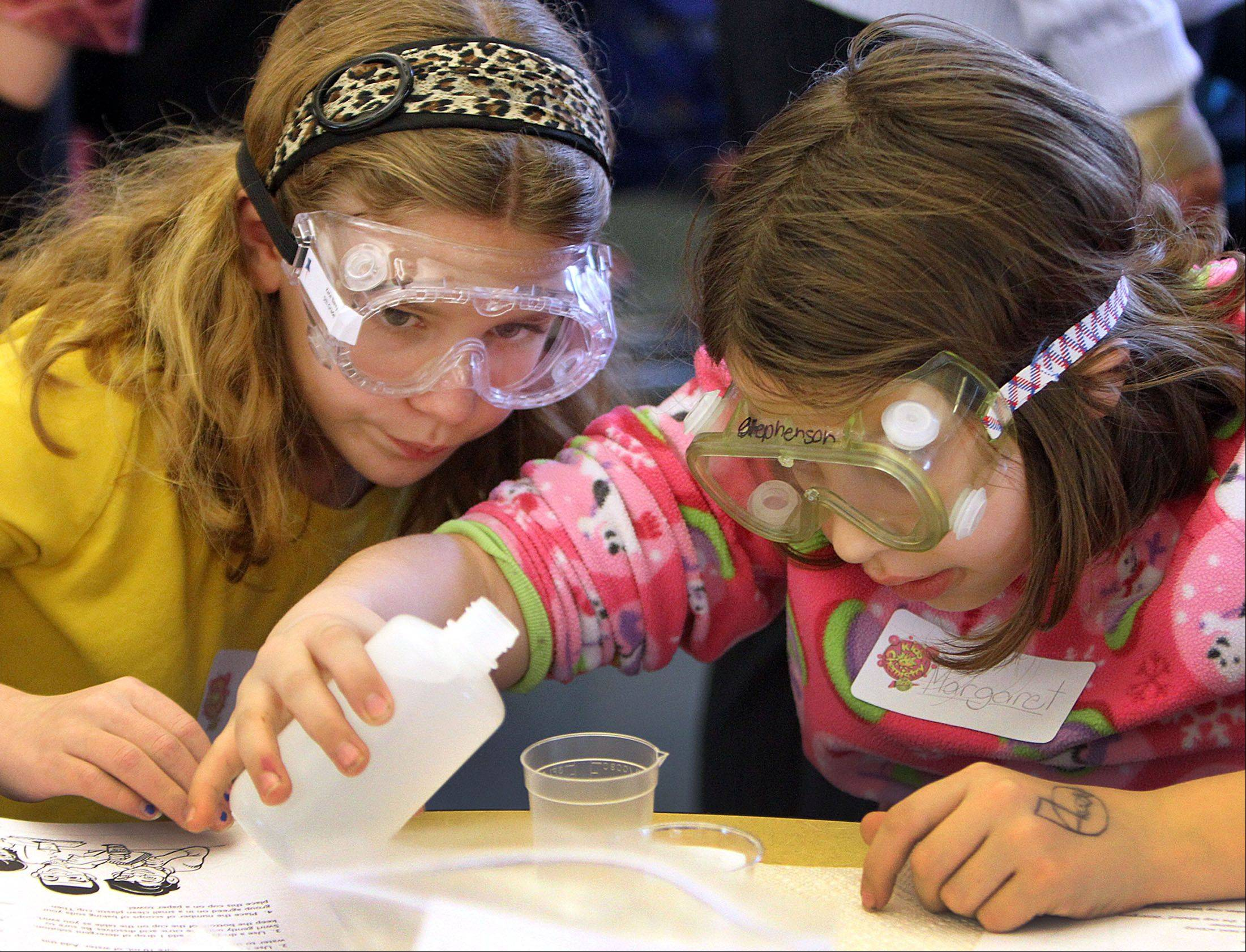 Copeland Manor School fifth-graders Kate Barry, left, and Margaret Stephenson participate in a science program called Kids in Chemistry on Thursday in Libertyville.