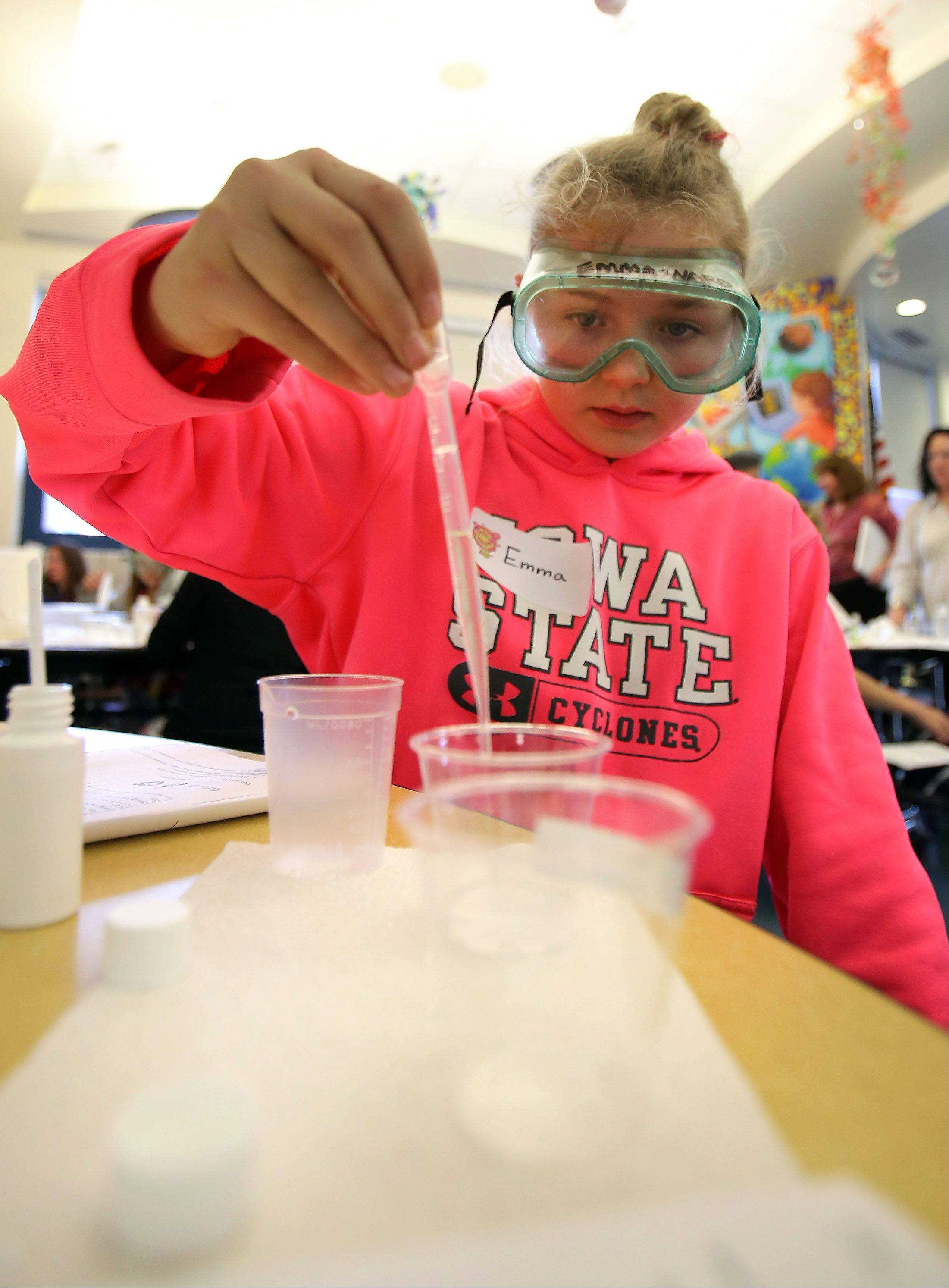 Fifth-grade student Emma Ward combines citric acid with water and baking soda on Thursday at Copeland Manor School.