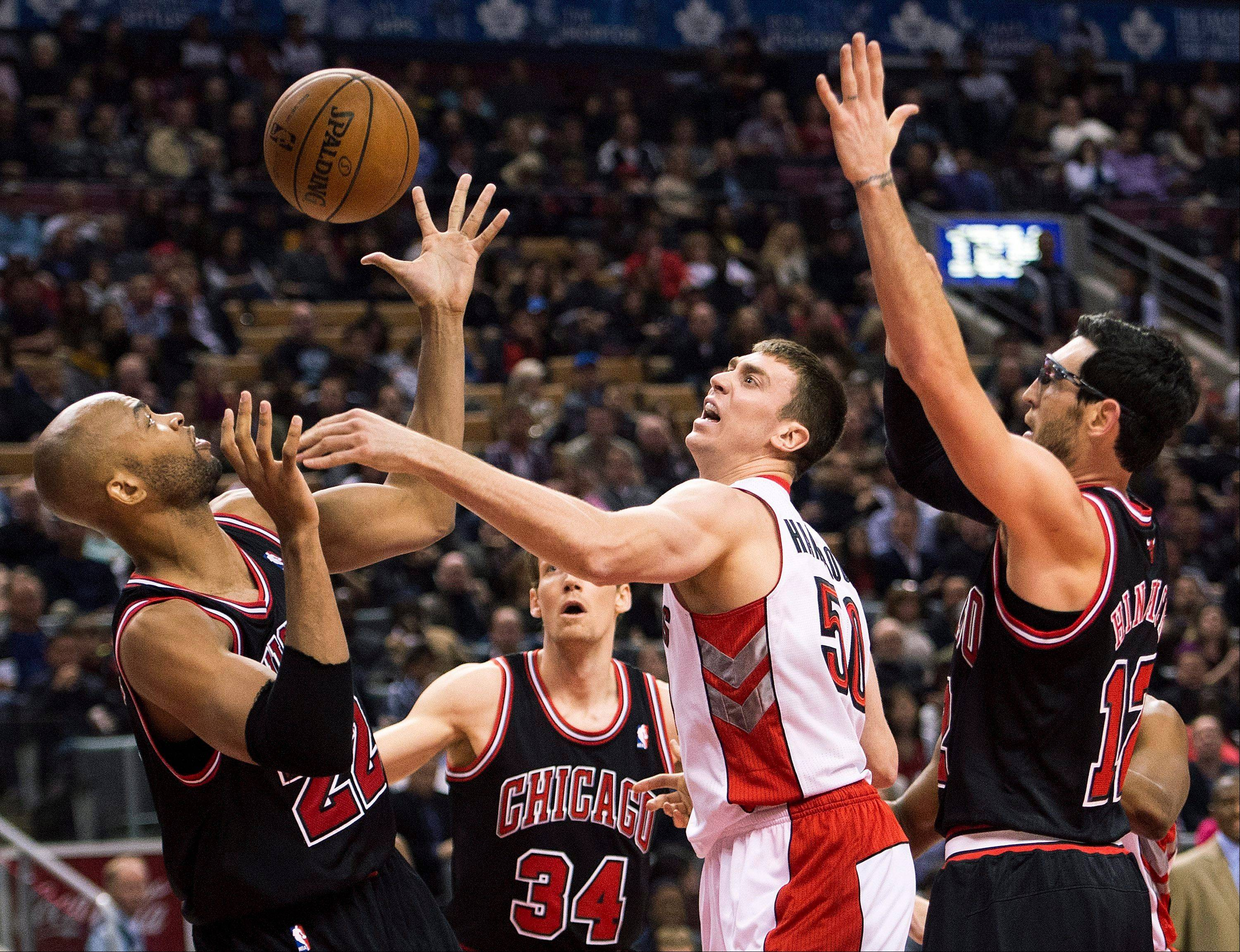Toronto Raptors forward Tyler Hansbrough, center, battles for the loose ball against Chicago Bulls' Taj Gibson, left, and Kirk Hinrich, right, during first-half NBA basketball game action in Toronto, Friday, Nov. 15, 2013.