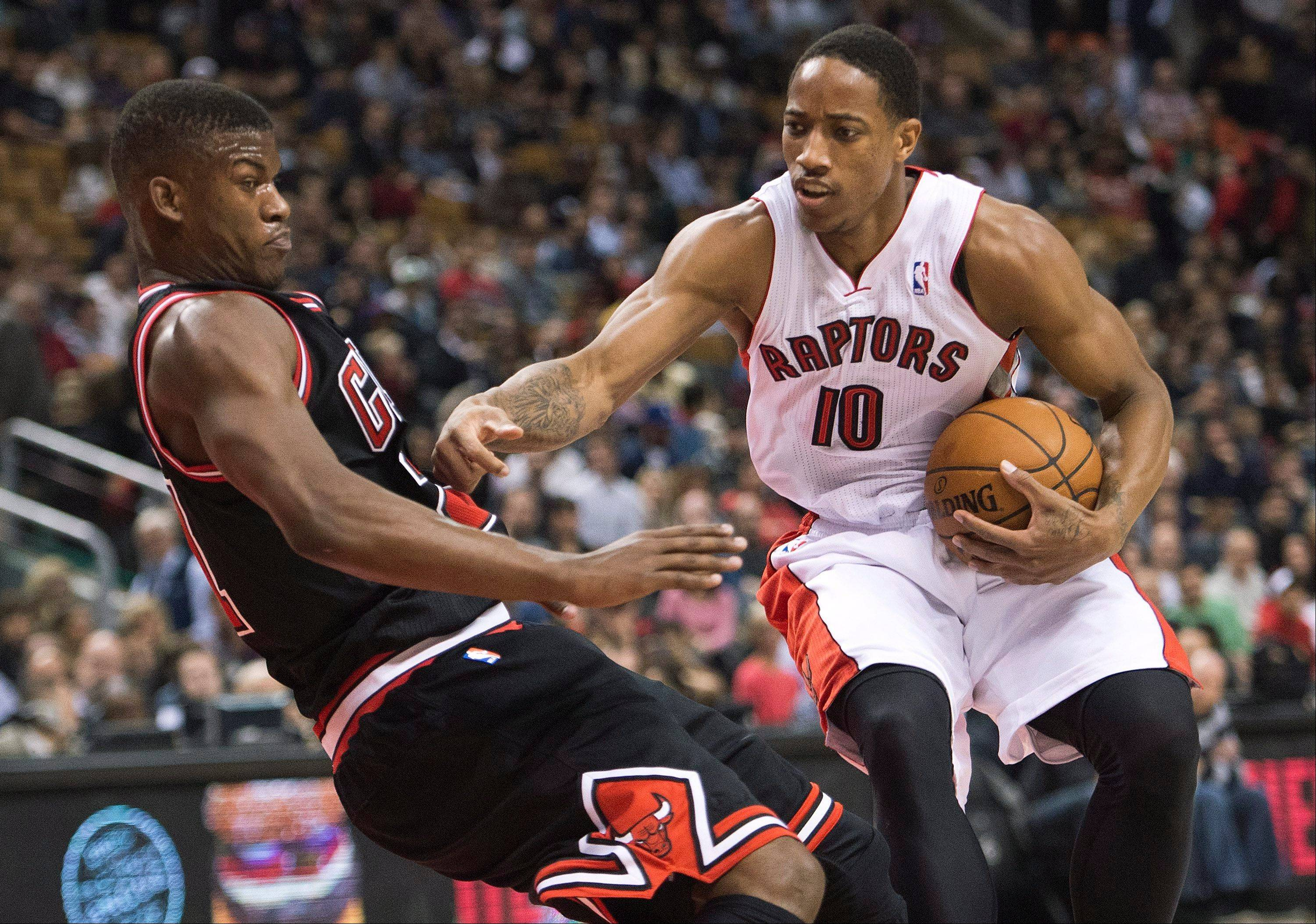 Toronto Raptors forward DeMar DeRozan, right, knocks down Chicago Bulls forward forward Jimmy Butler, left, during first-half NBA basketball game action in Toronto, Friday, Nov. 15, 2013.
