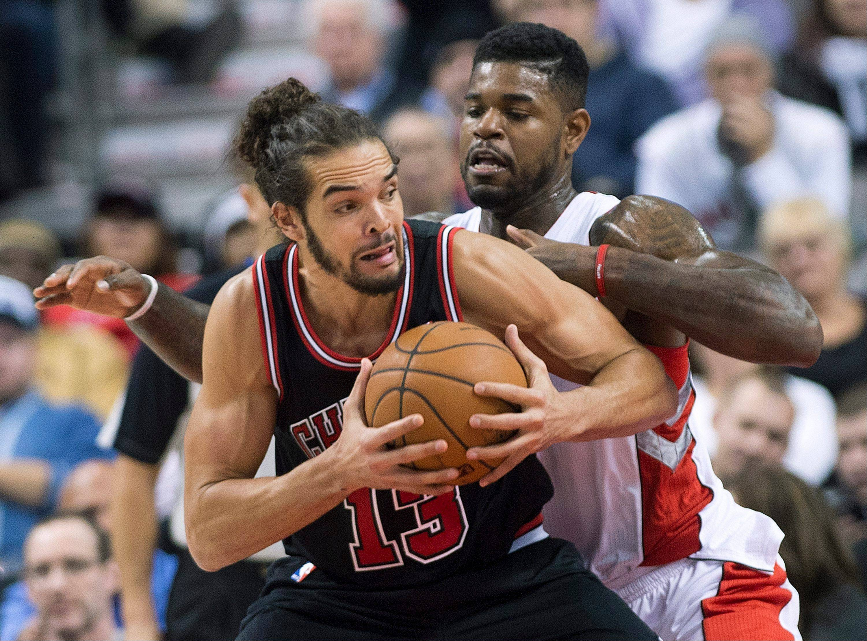 Toronto Raptors forward Amir Johnson, back, guards against Chicago Bulls forward Joakim Noah, front, during first-half NBA basketball game action in Toronto, Friday, Nov. 15, 2013.