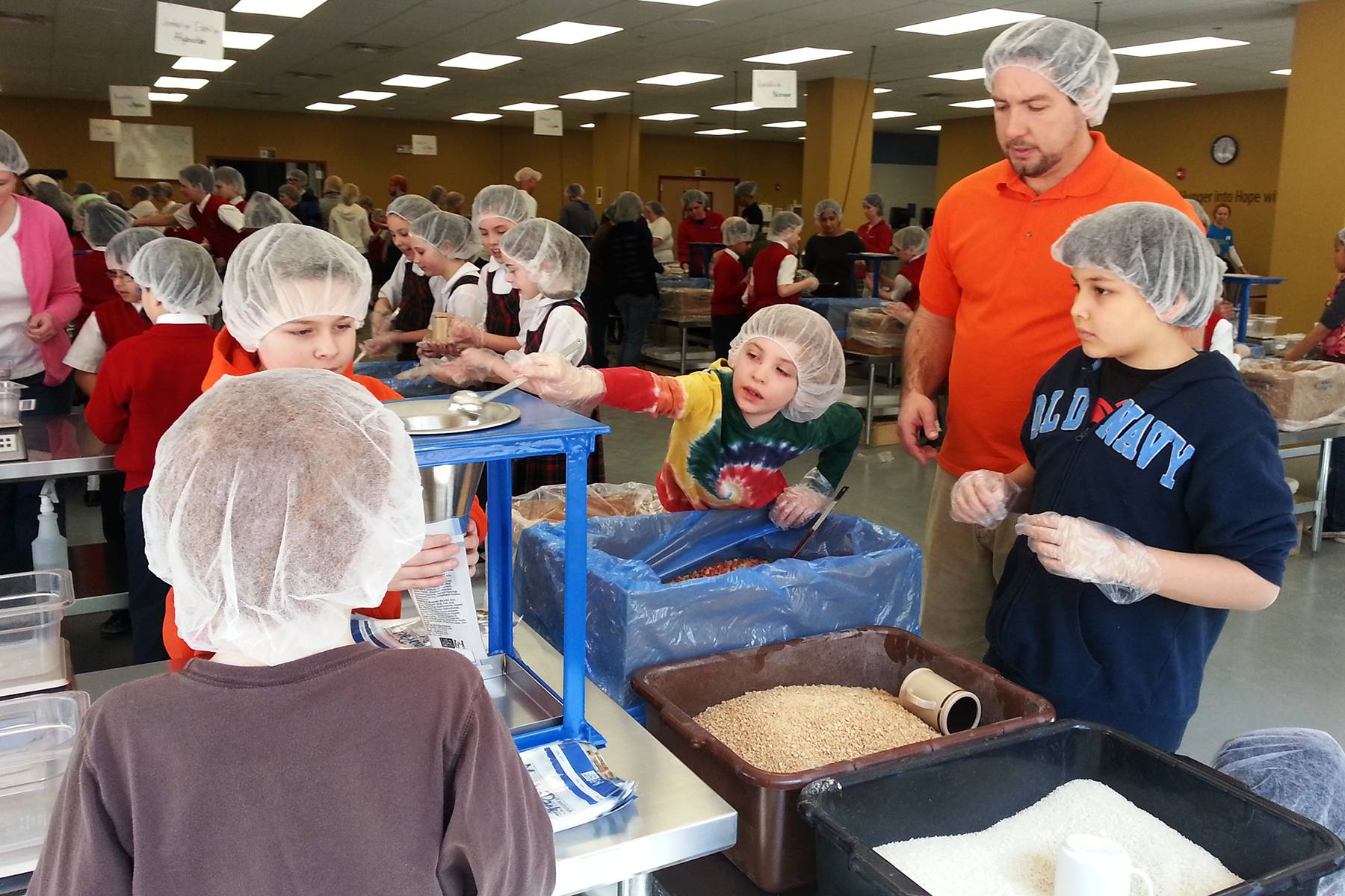 Students from Country Meadows Montessori School hand-pack meals to be shipped to around the world by Feed My Starving Children as part of an ongoing service project to help the hungry.
