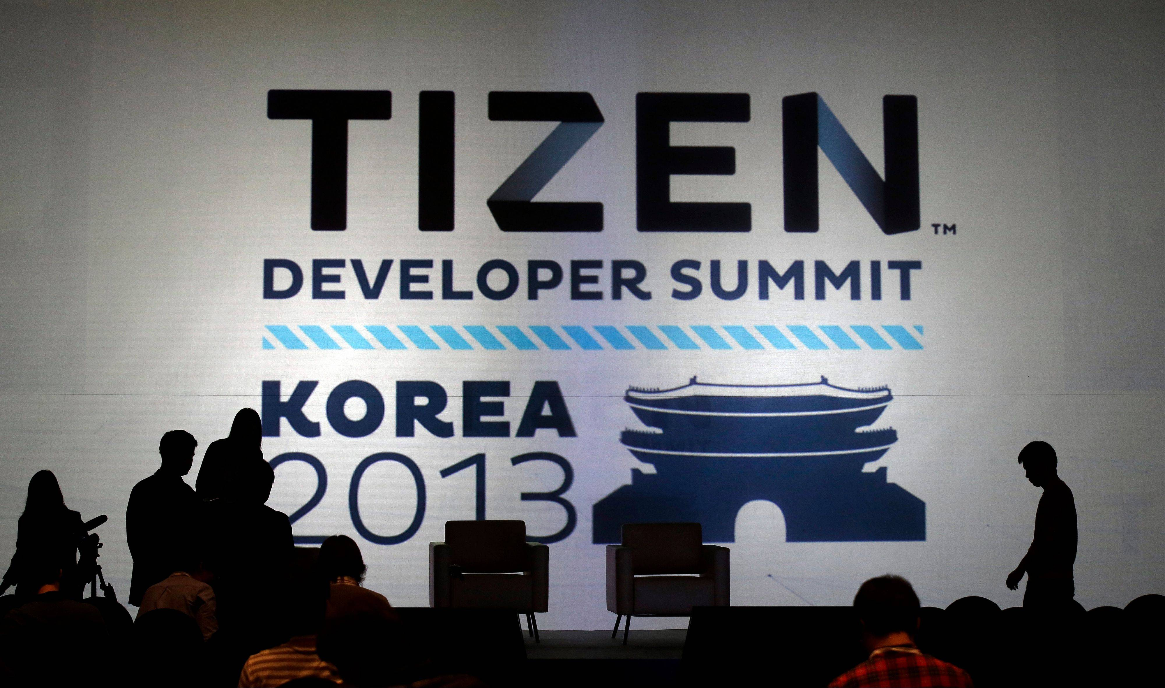 Participants are seen near the logo of Tizen Monday during the Tizen Developer Summit 2013 in Seoul, South Korea. Samsung is in a quiet push to make its Tizen operating system a part of the technology lexicon as familiar as Google�s Android or Apple�s iOS. Its ambition doesn�t stop there. Samsung sees the software in your car, fridge and television too. The first developer conference in Asia for Tizen wrapped up Tuesday after a two-day run, bringing together app developers and Tizen backers from Samsung, Intel and mobile operators.