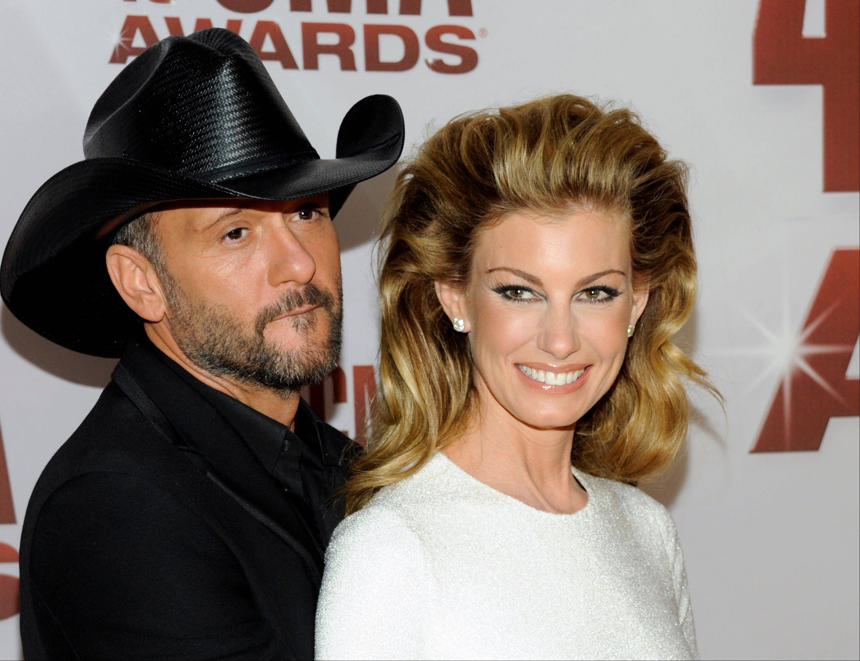 This Nov. 9, 2011 file photo shows country singers Tim McGraw, left, and his wife Faith Hill at the 45th Annual CMA Awards in Nashville, Tenn. McGraw and Hill are brushing off divorce rumors as they power into a new round of Soul2Soul duet performances in Las Vegas. The country music royals sat close and joked with each other about tabloid headlines during a round table interview with reporters before their Friday show at the Venetian casino.