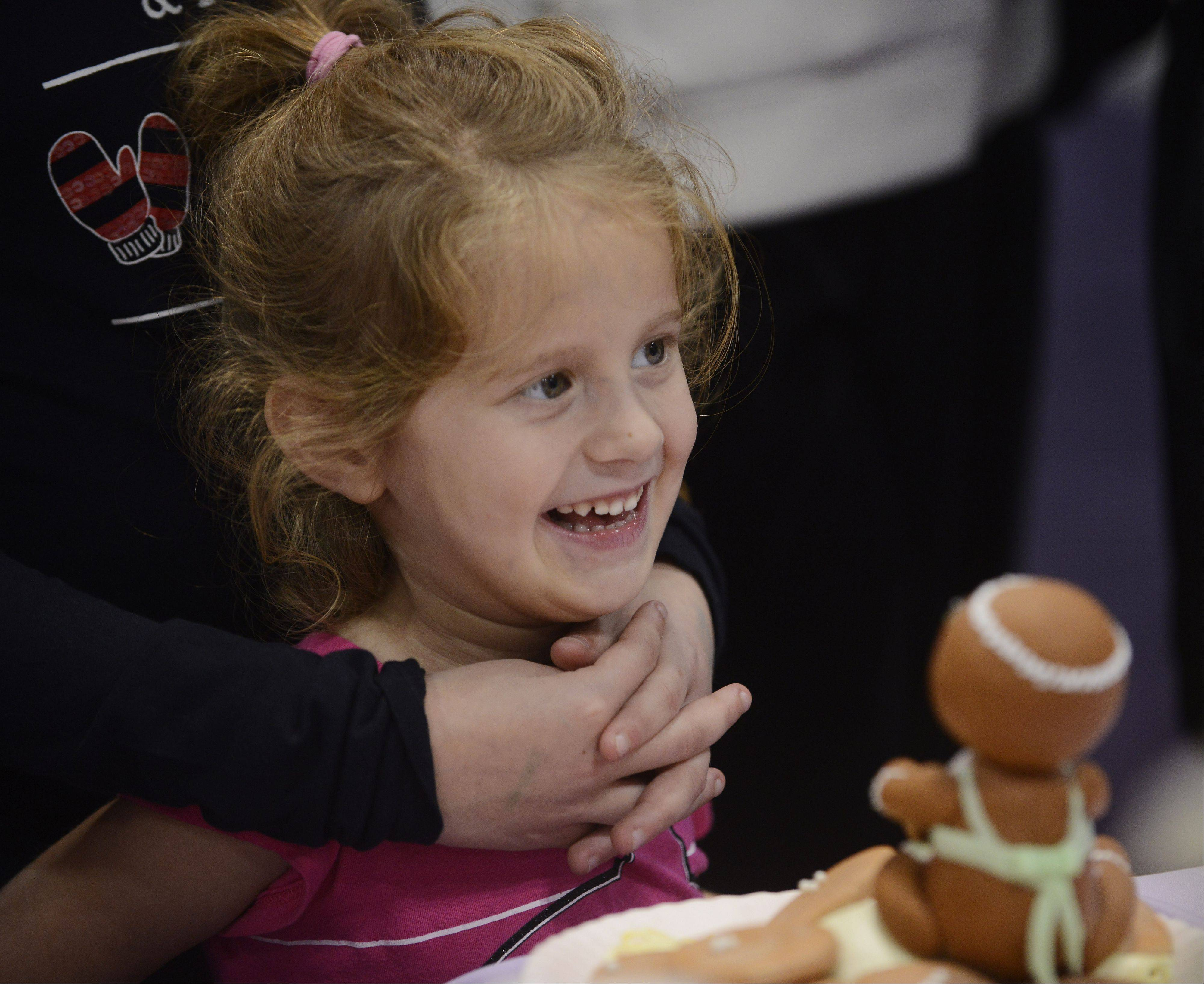Riley Penar, 4, of Elgin smiles while watching a cake-decorating demonstration by the Wilton School of cake decorating and confectionery art Saturday during the America's Baking and Sweets Show at the Renaissance Schaumburg Convention Center.