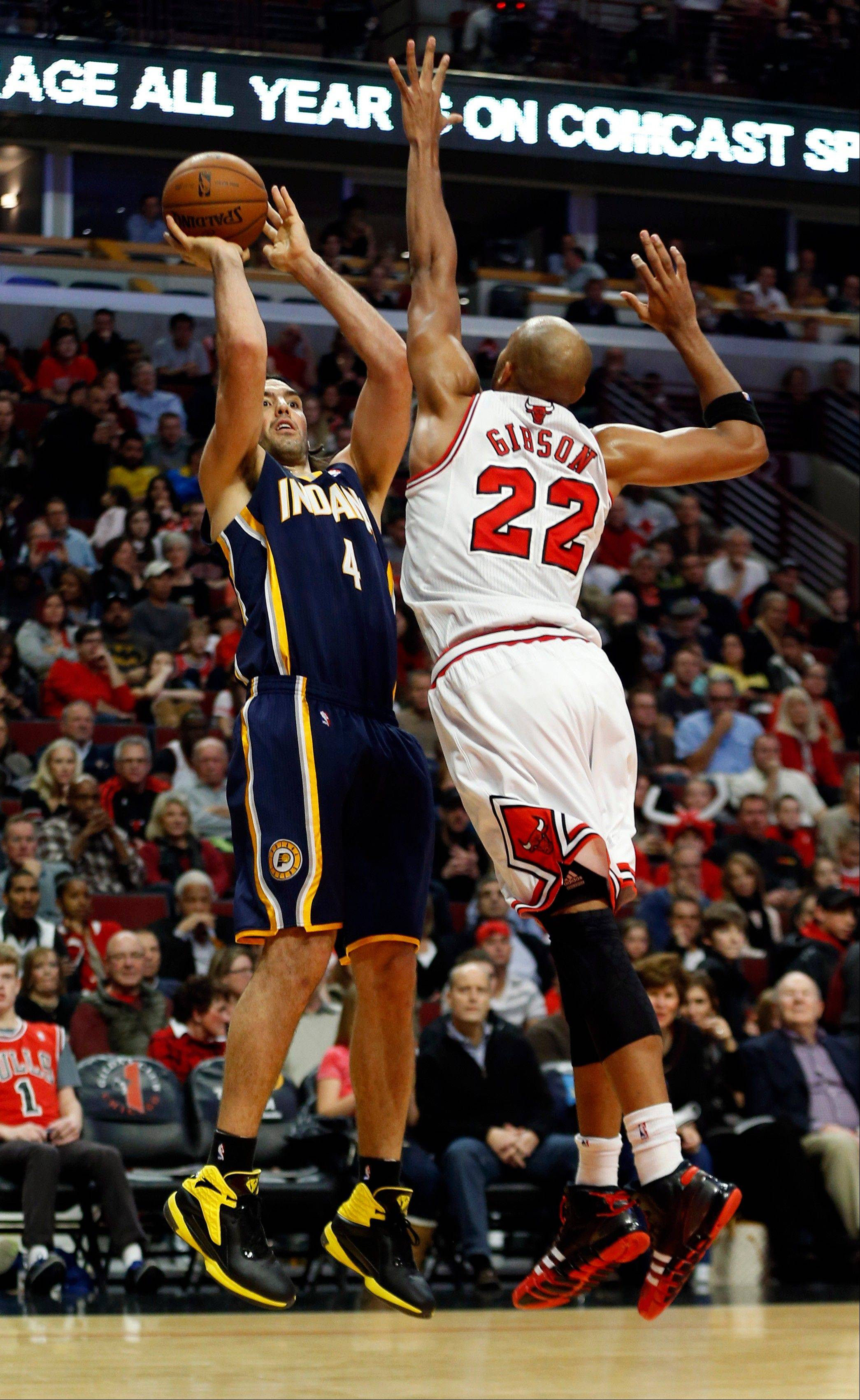 Indiana Pacers forward Luis Scola (4) shoots against Bulls forward Taj Gibson (22) during Saturday night�s game at the United Center. The Bulls ended the Pacers perfect season with a 110 to 94 win.