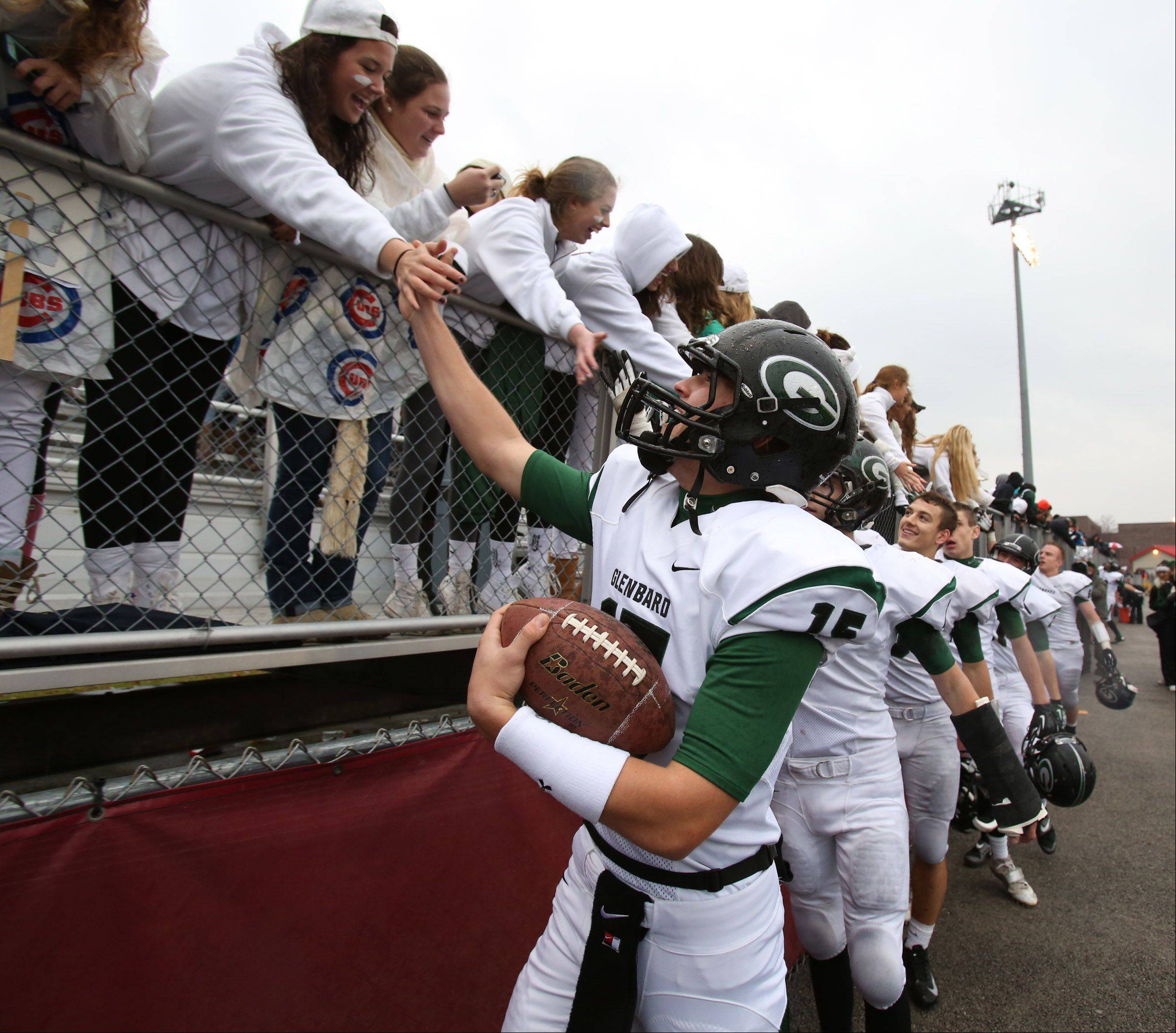 Glenbard West quarterback Kevin Dawrant celebrates with fans as Glenbard West wins 42-21 over Schaumburg in a quarterfinal playoff game on Saturday, November 16th, in Schaumburg.