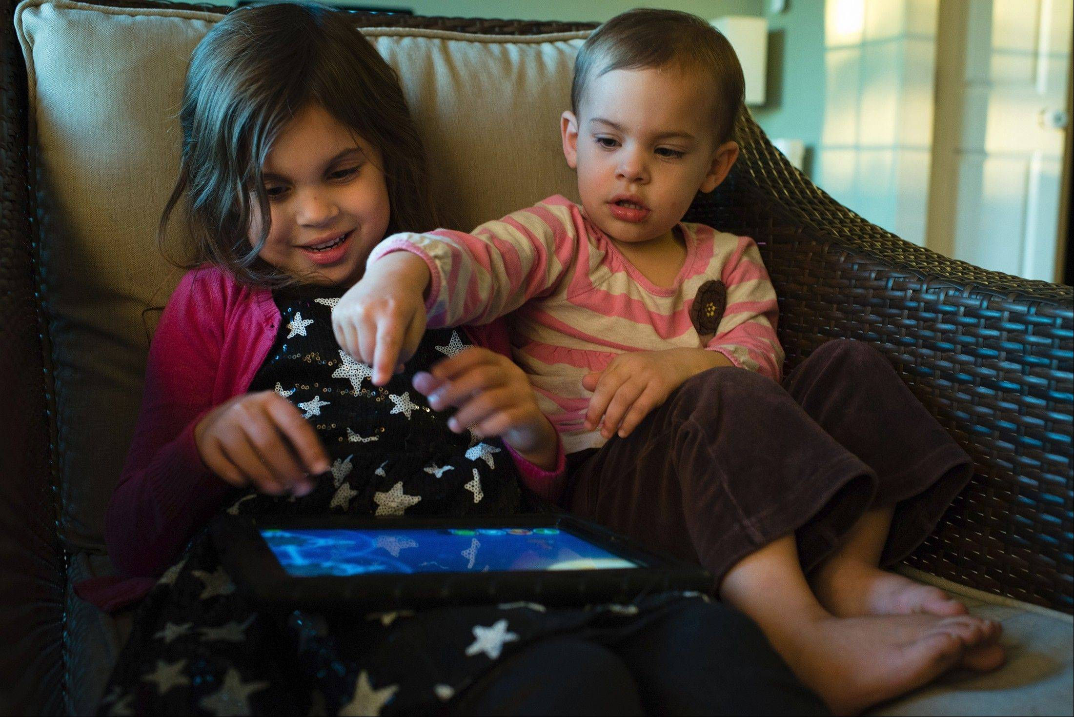 Kaylie Zaal, 5, left, and her little sister, Reagan, 2, play on an iPad at their home in Middletown, Md. Manufacturers are racing to tap into the market for kid-friendly tablets.