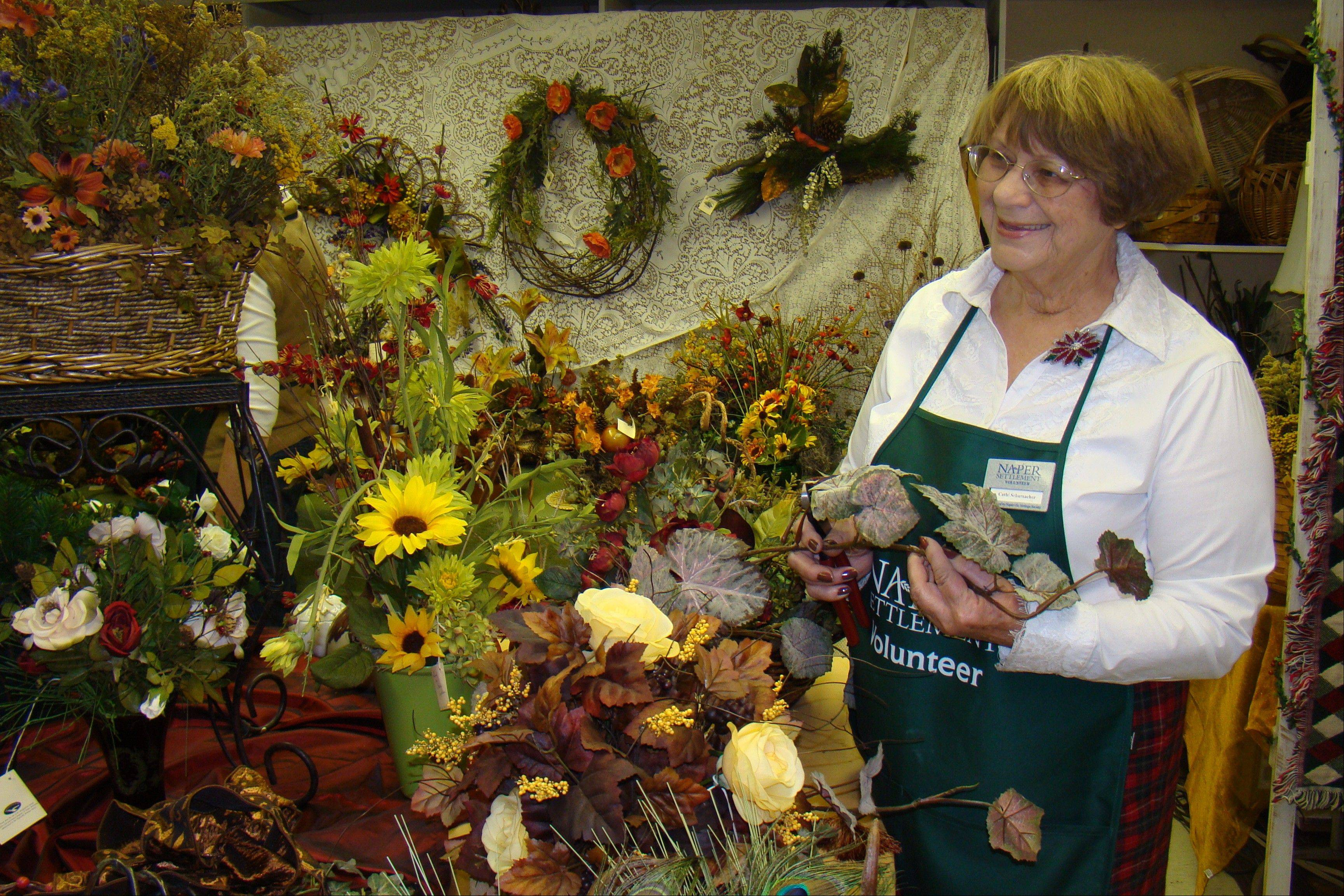 Cathi Schumacher, a member of the Weed Ladies volunteer floral designing group, looks over some floral arrangements, as the group prepares for its annual Winter Show and Sale at the Naper Settlement.