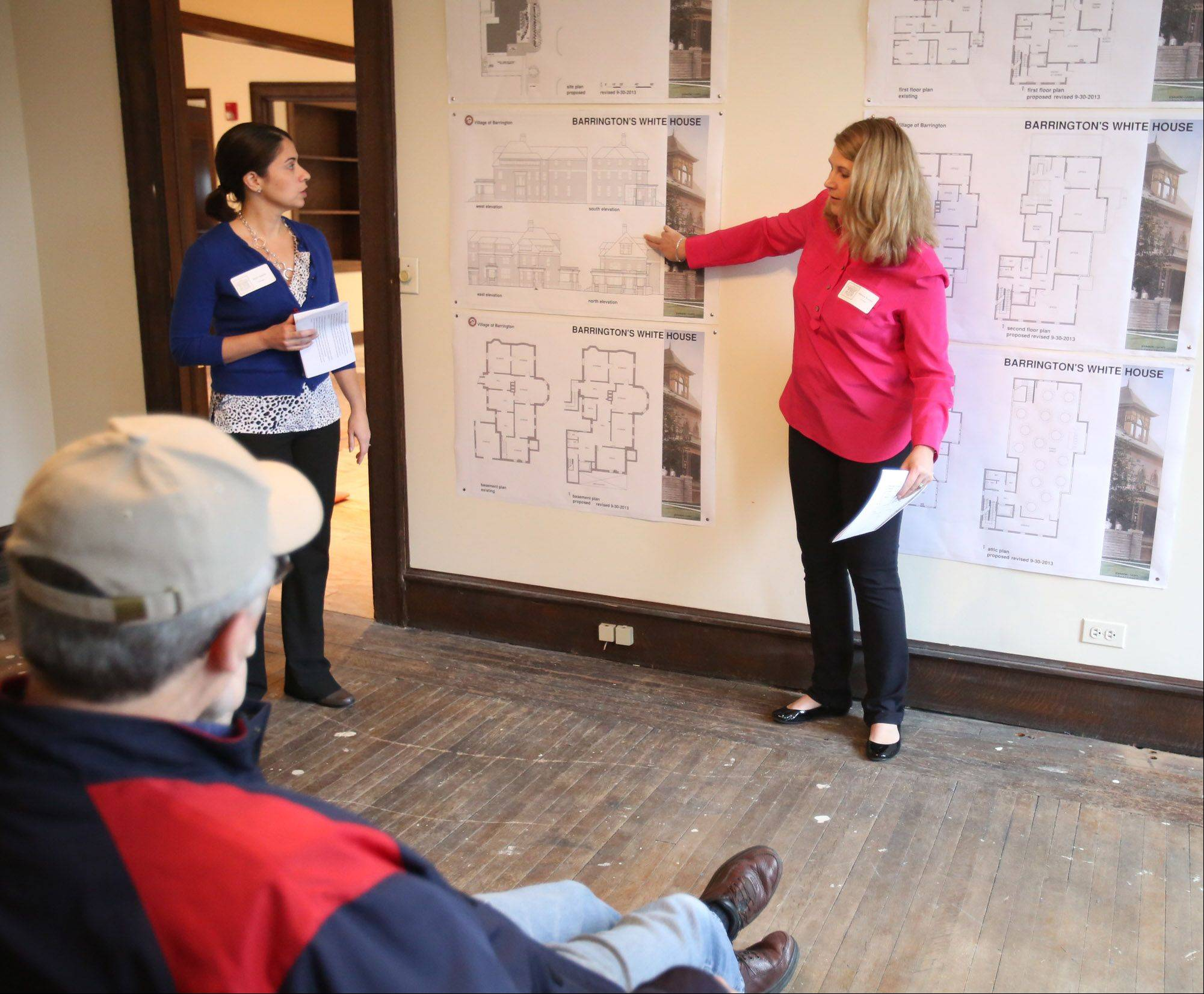 Volunteers April Goshe, left, and Melissa Buckley, both of Barrington, explain renovation plans for the White House during a community open house Saturday. The open house runs through Sunday.
