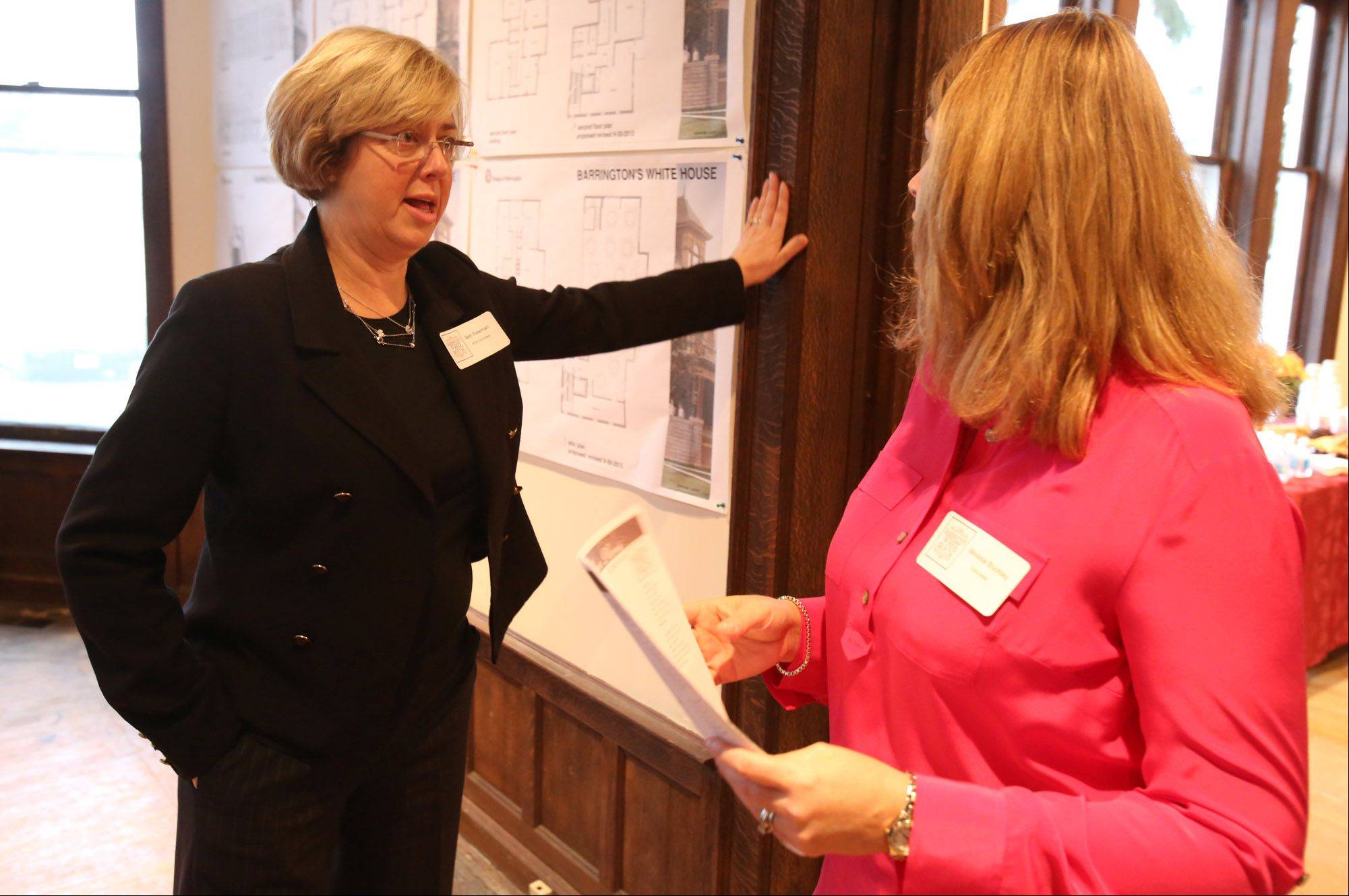 Beth Raseman, a Barrington White House board member, discusses woodwork with Melissa Buckley of Barrington during a community open house Saturday.