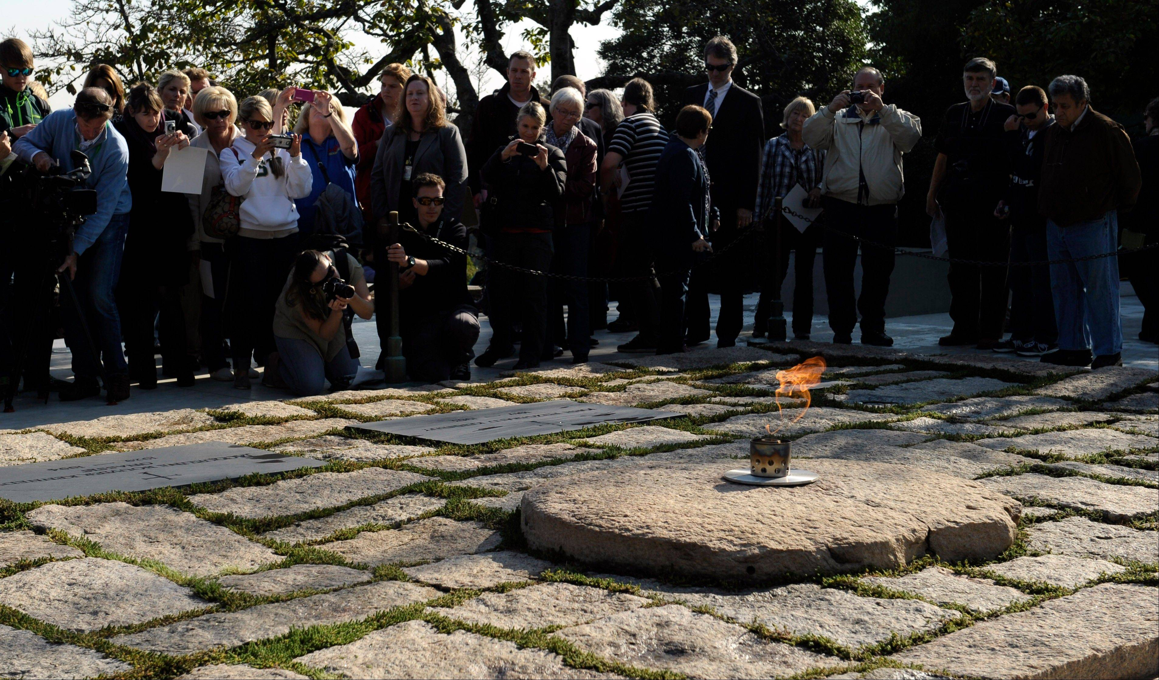 People visit the eternal flame at the gravesite of former President John F. Kennedy as it burns at Arlington National Cemetery in Arlington, Va.