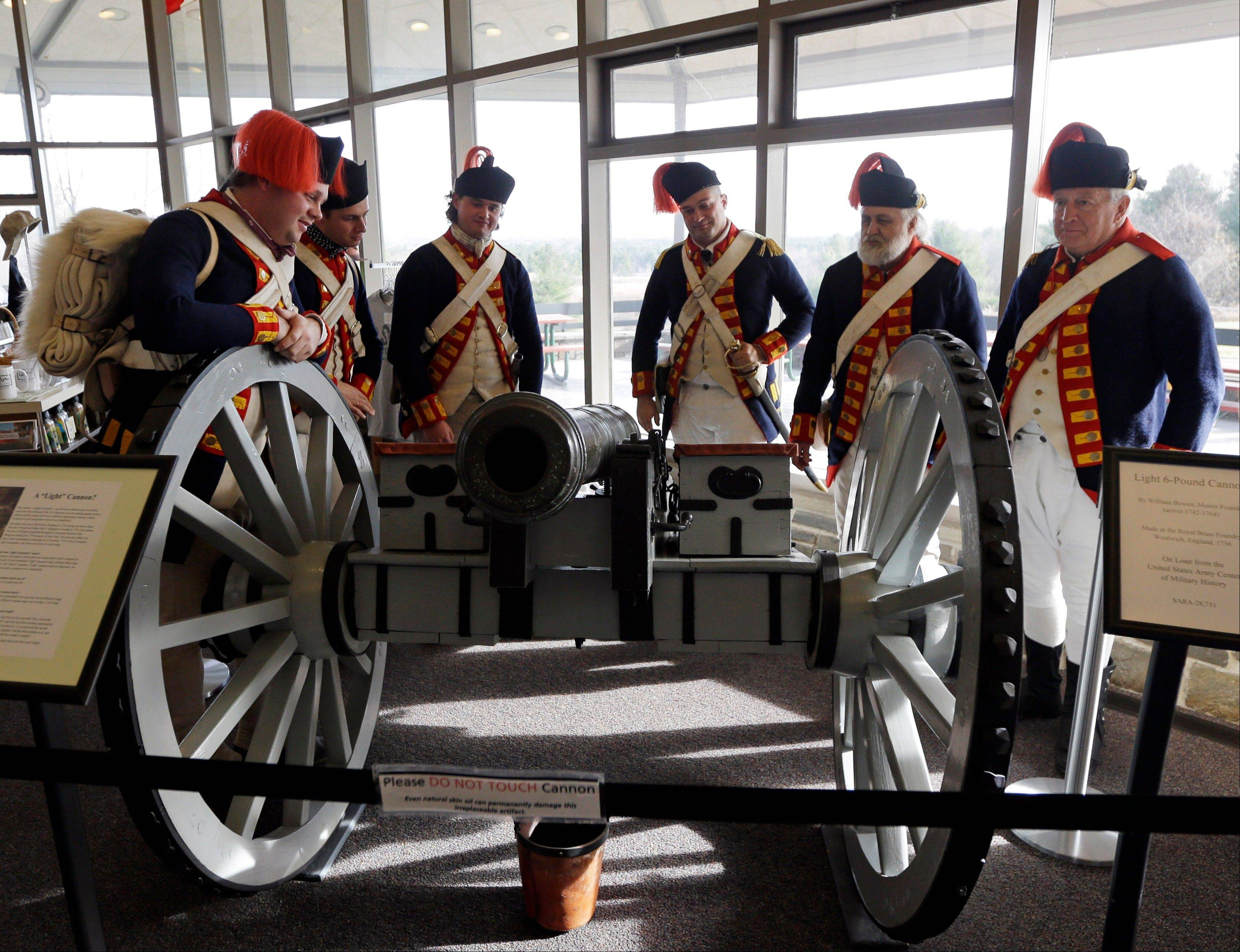 Revolutionary War re-enactors dressed as Royal regimental artillery soldiers stand behind a cannon after unveiling it Friday during a ceremony at Saratoga National Historical Park, in Stillwater, N.Y.