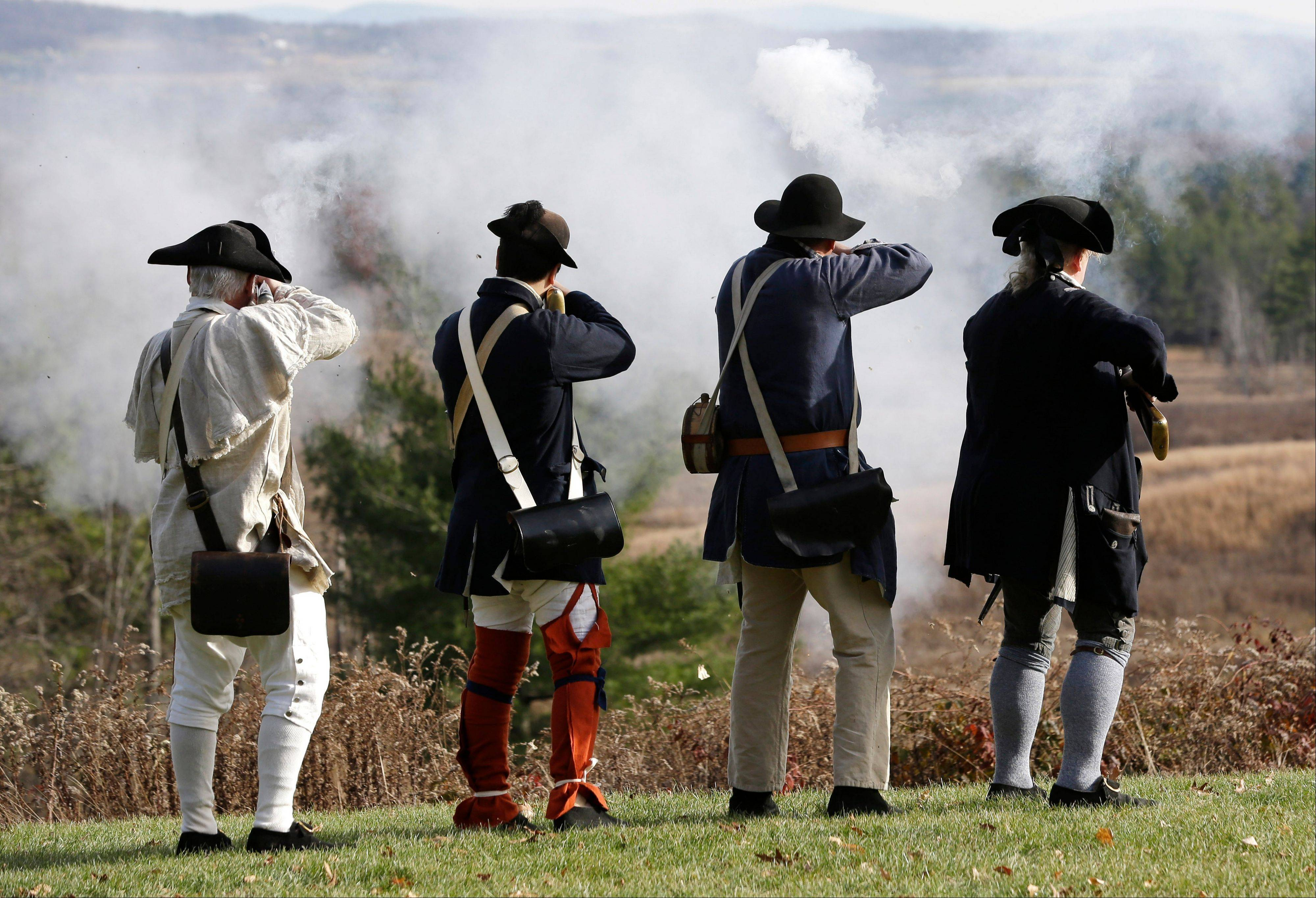 Revolutionary War re-enactors fire shots before a ceremony for the cannon. The cannon surrendered by the British after the Battles at Saratoga is back at the battlefield after stints in museums and private collections in four states over the past half-century.