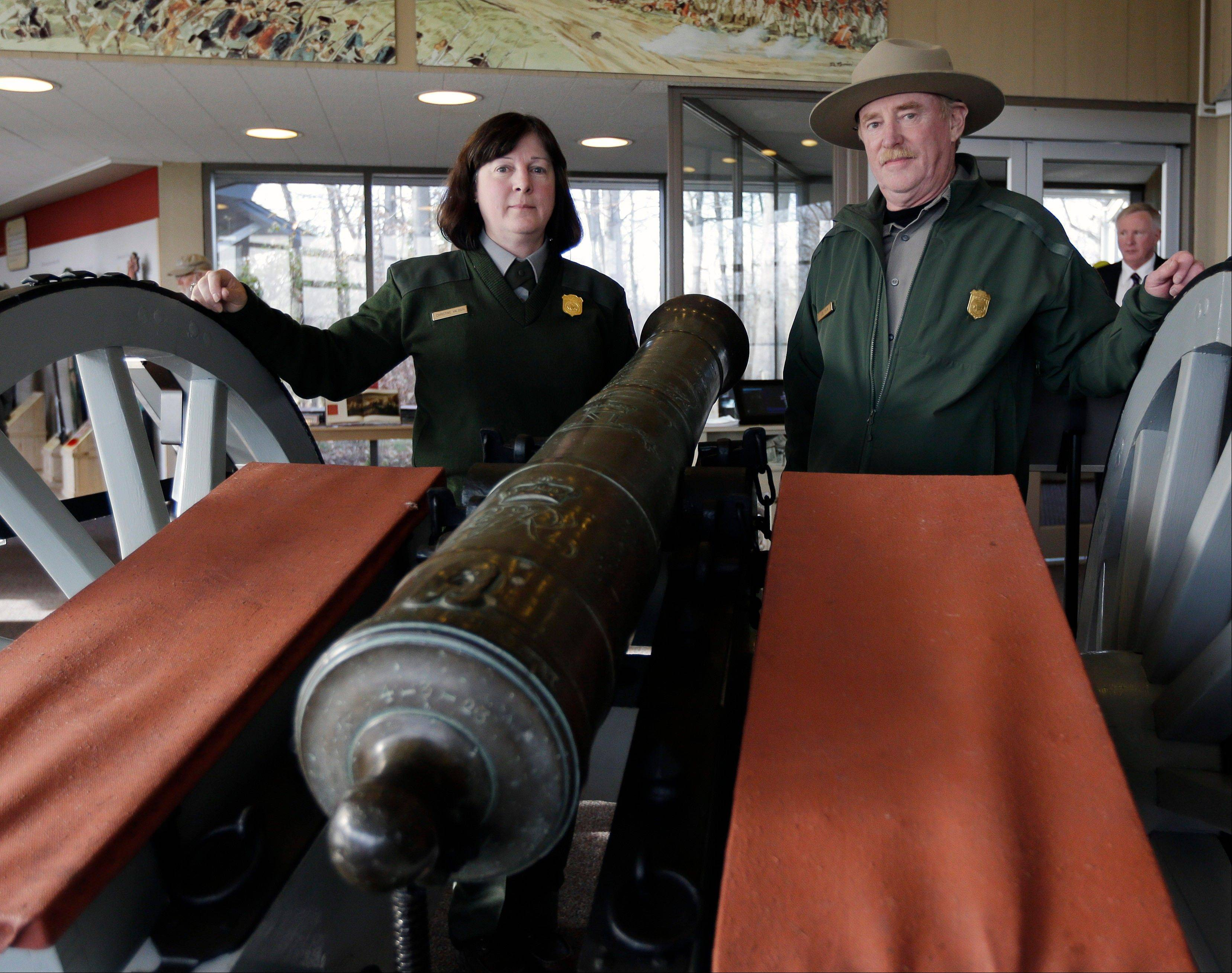 Saratoga National Historical Park Curator Christine Valosin, left, and superintendent Joe Finan pose with the Revolutionary War cannon after the ceremony. Officials at Saratoga say the rare Revolutionary War cannon was tracked down to Alabama's Tuscaloosa Museum of Art and recently delivered to the park, located 20 miles north of Albany.