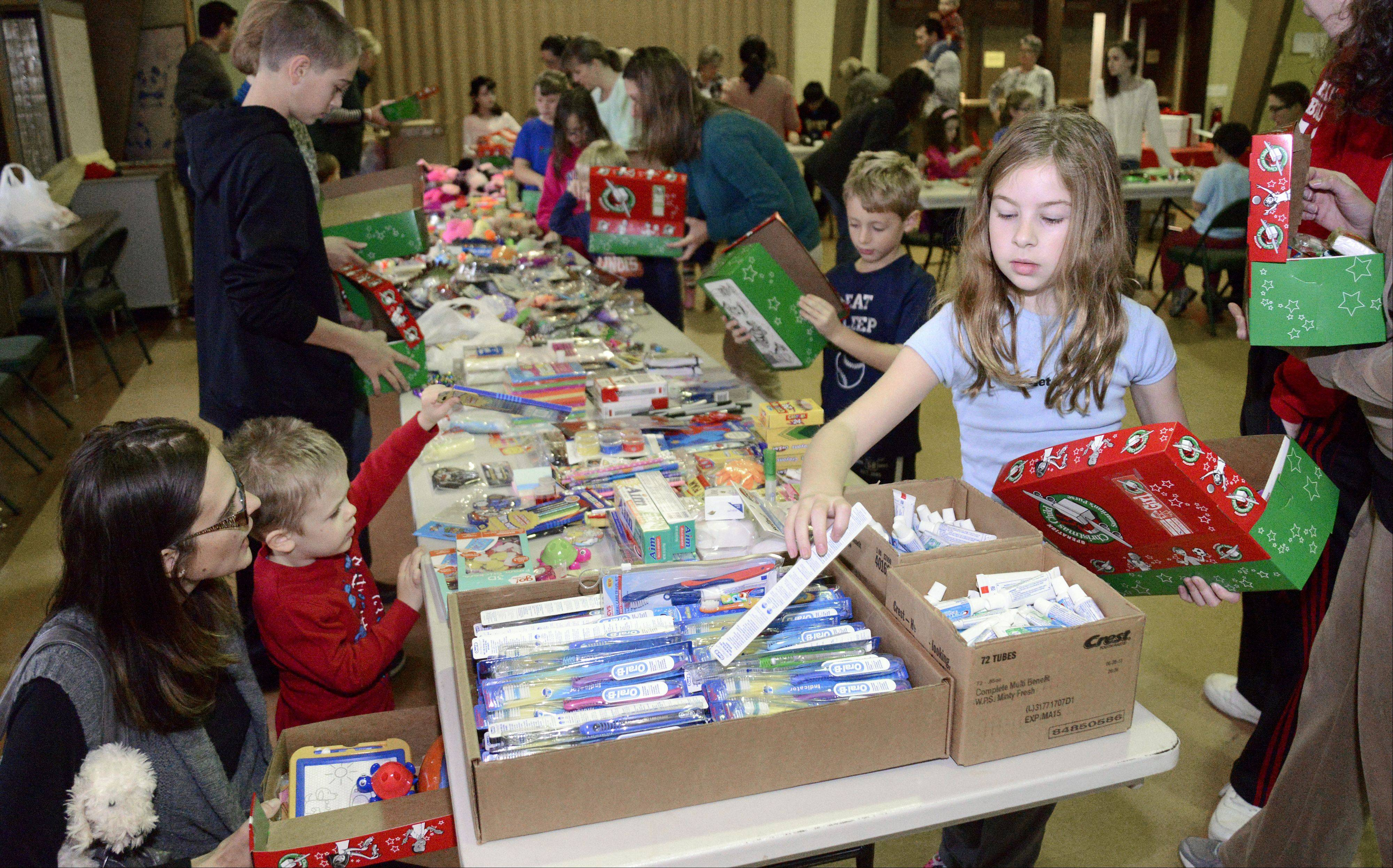Jen Katsenios and her 3-year-old son, TJ, of Elgin, left, and Kelsie Hoffmann, 9, of Batavia fill shoe boxes full of goodies at the Operation Christmas Child packing party at St. Mark's Preschool in St. Charles on Saturday. TJ attends the preschool. It was his first time at the event.