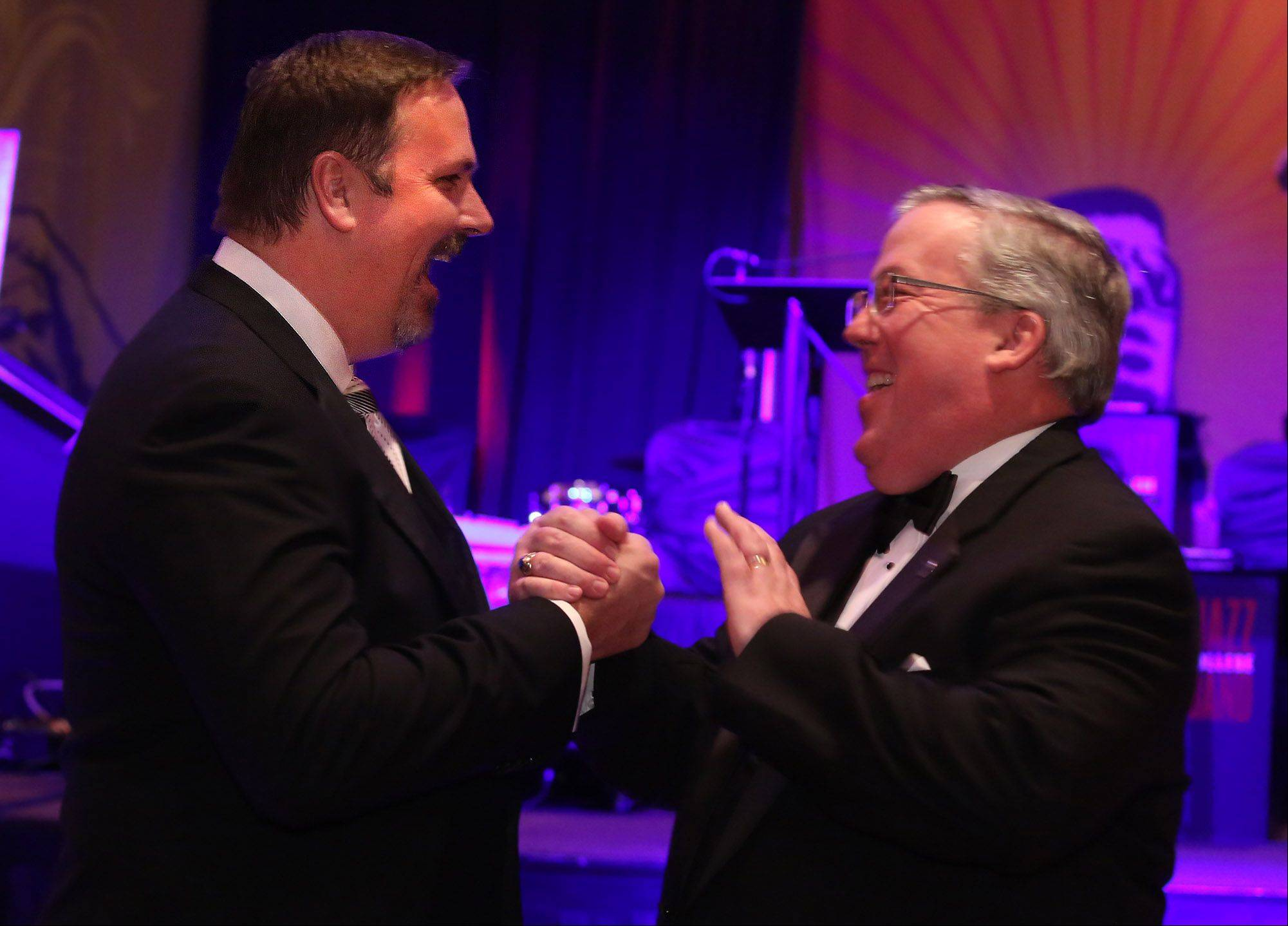 Robert O'Meara, president of Shelter, Inc. board of directors, of Barrington, right, speaks with Richard Sykes of Inverness before O'Meara presented Sykes with the Paul Buckholz award at the Shelter Ball at the Hyatt Recency on Friday in Schaumburg.