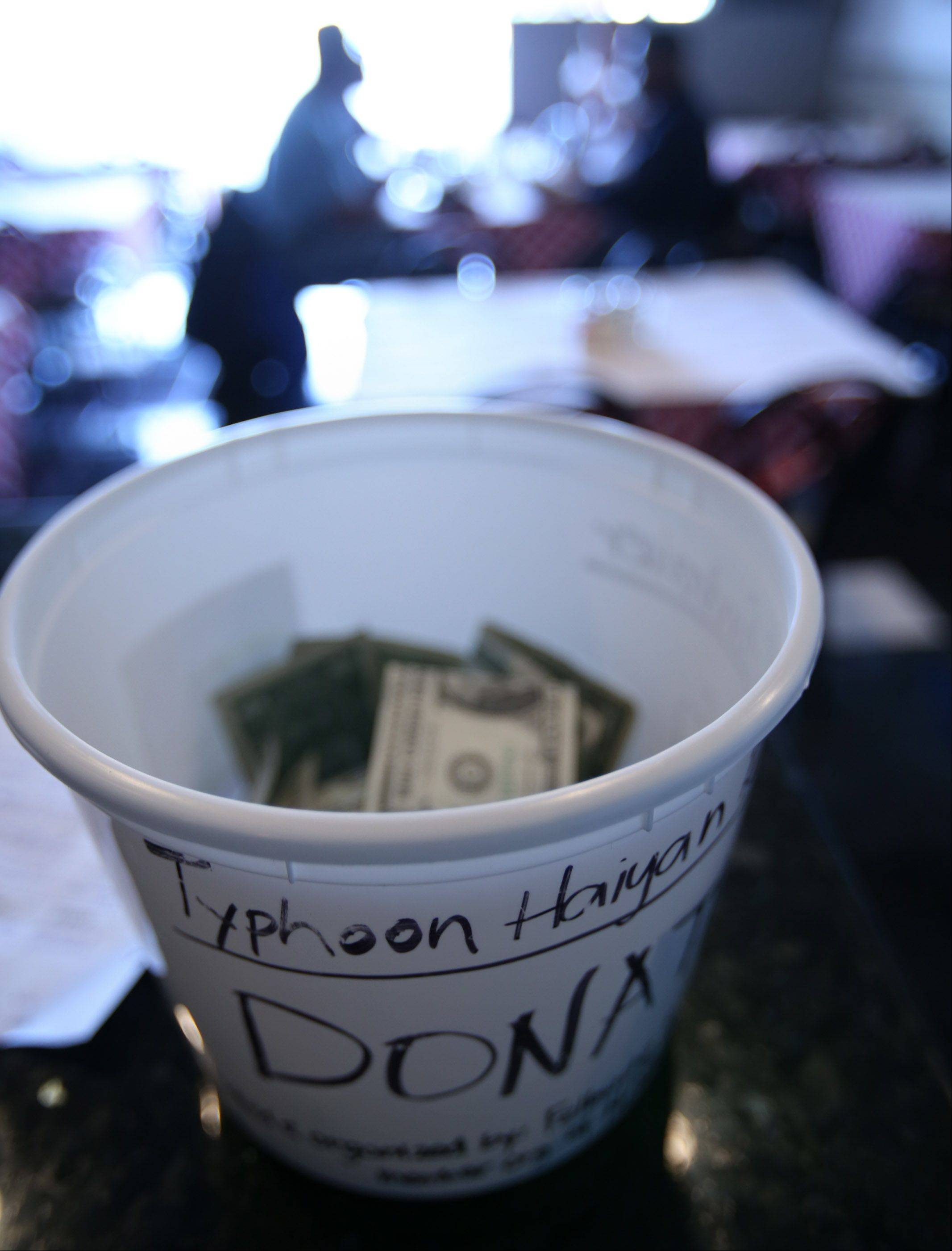 A bucket for a fund drive for typhoon victims in the Philippines sits on the front counter at Allegretti's Pizza in Des Plaines.