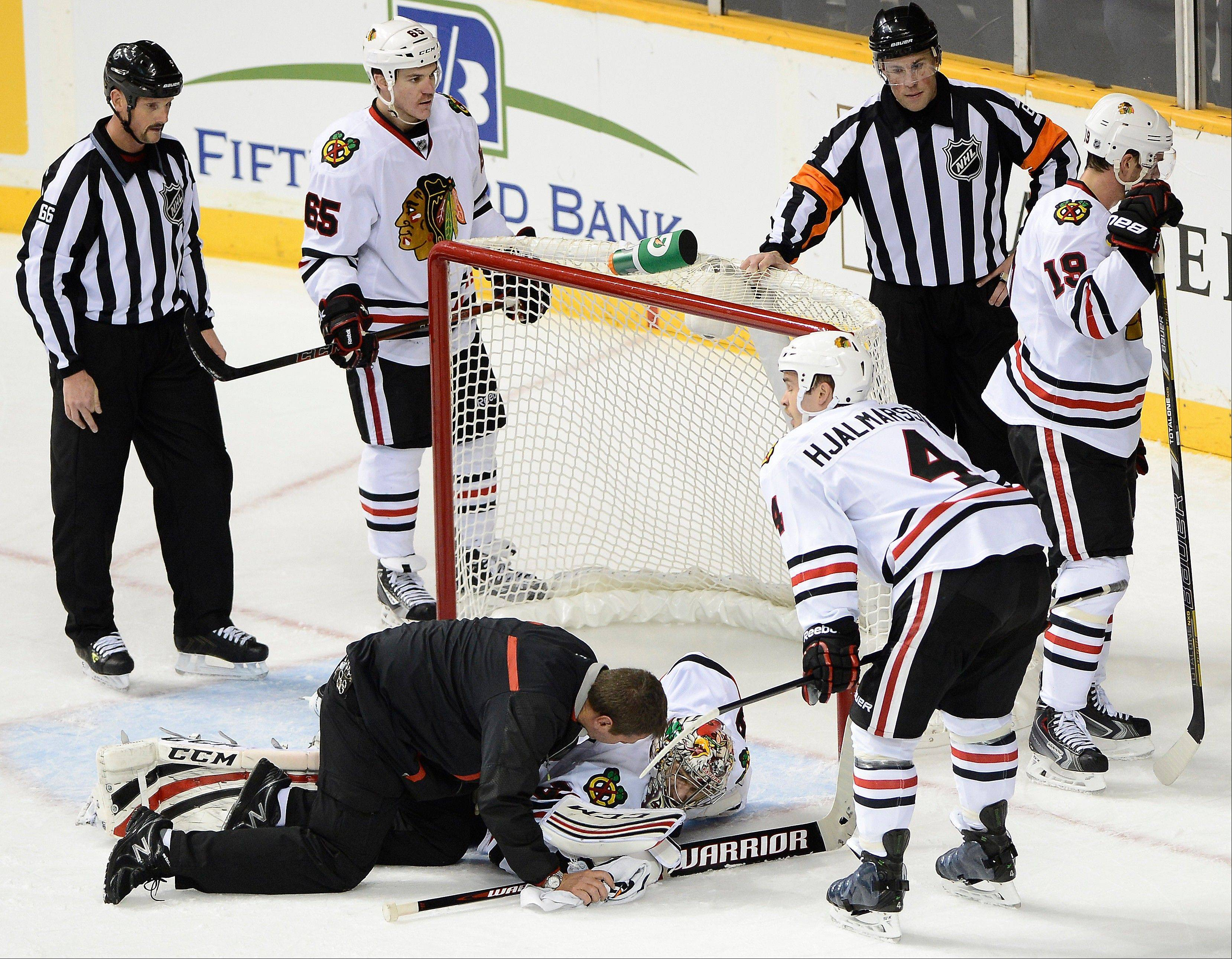Blackhawks goalie Nikolai Khabibulin is attended to after injuring his left leg in the first period Saturday night.