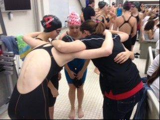Palatine coach Brittany Berleman joins the huddle before the Pirates' 400-yard freestyle relay on Saturday at Barrington.