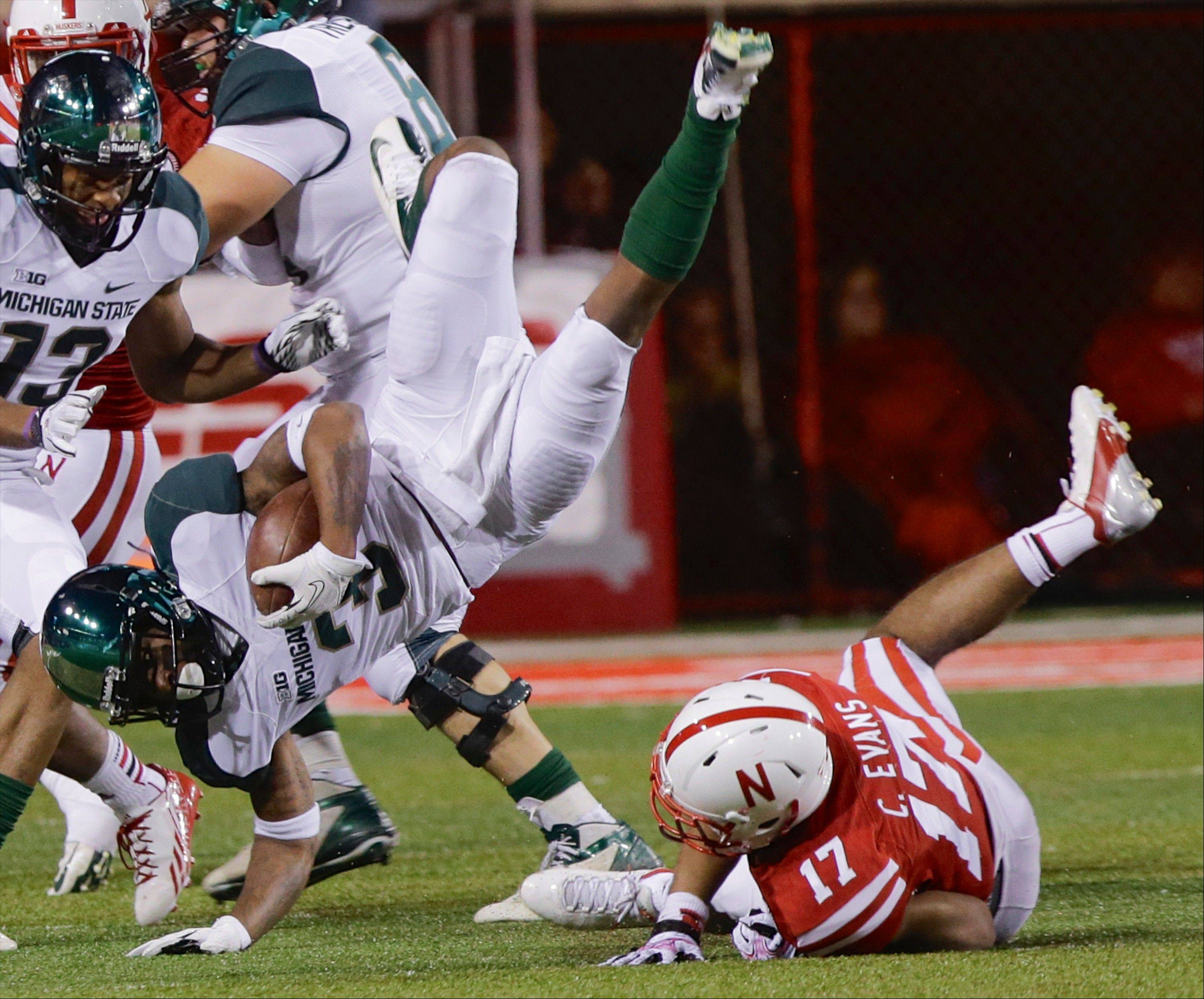 Michigan State wide receiver Macgarrett Kings (3) is upended by Nebraska cornerback Ciante Evans (17) during Saturday's game in Lincoln, Neb. Michigan State won 41-28.