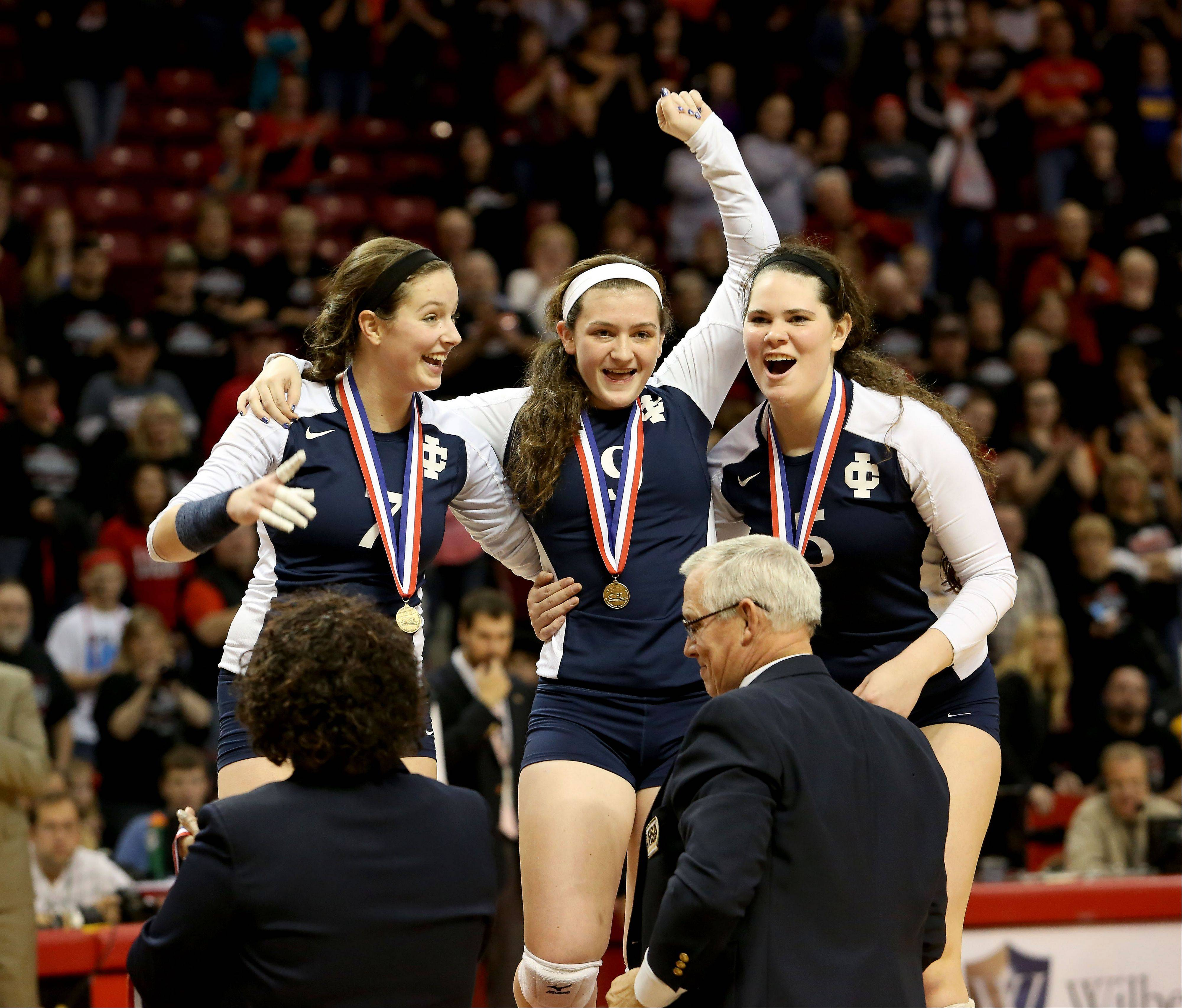 Delaney D'Amore, left and Rory Manion, right, help Frannie Cervone of IC Catholic up to get her medal after she was injured late in the second game against Edwards County in the Class 2A championship girls volleyball match on Saturday in Normal.