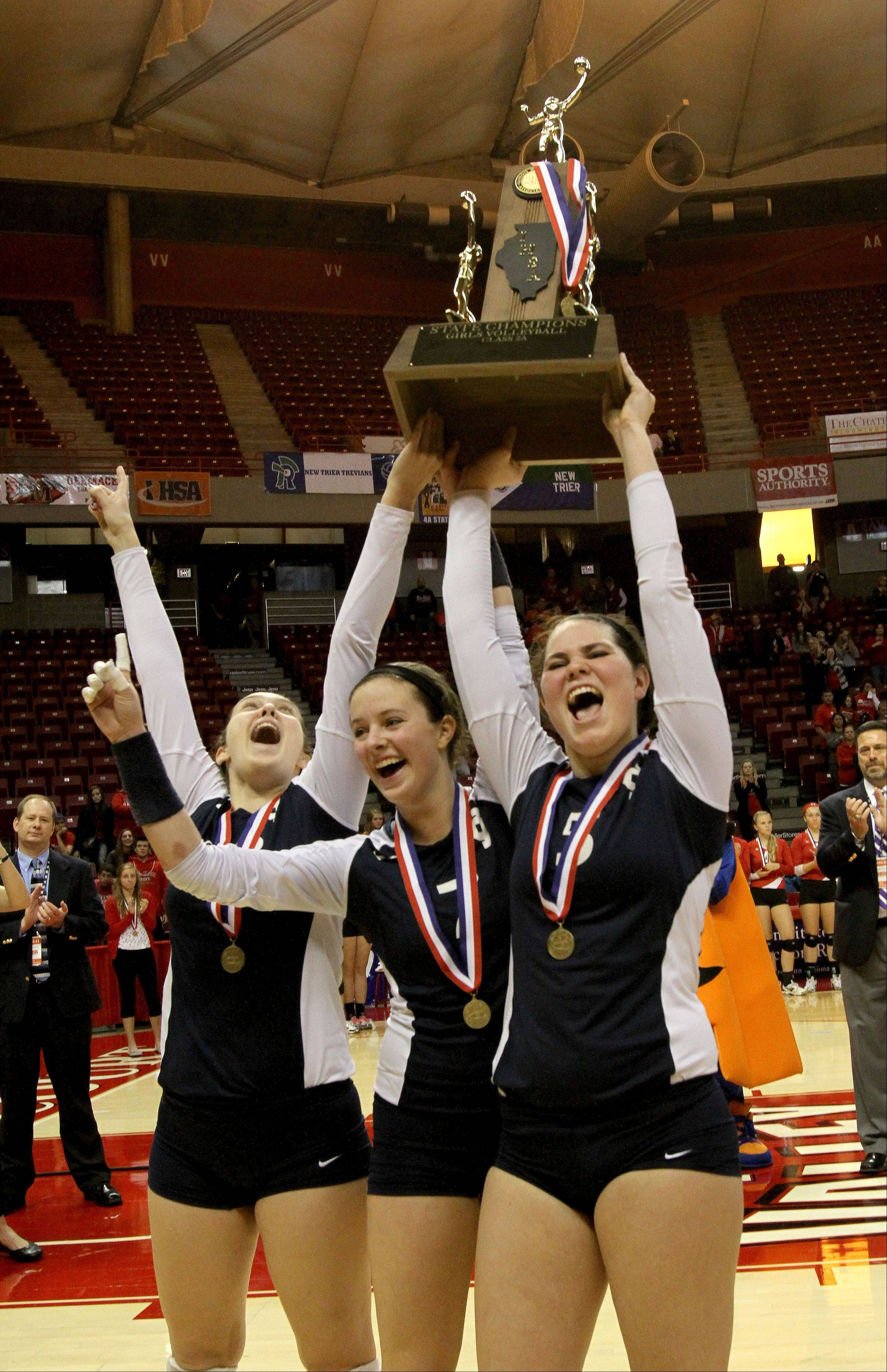 Left to right, Kimmy Martino, Delaney D'Amore and Rory Manion of IC Catholic hold up the trophy after beating Edwards County for the Class 2A championship in girls state volleyball on Saturday in Normal.