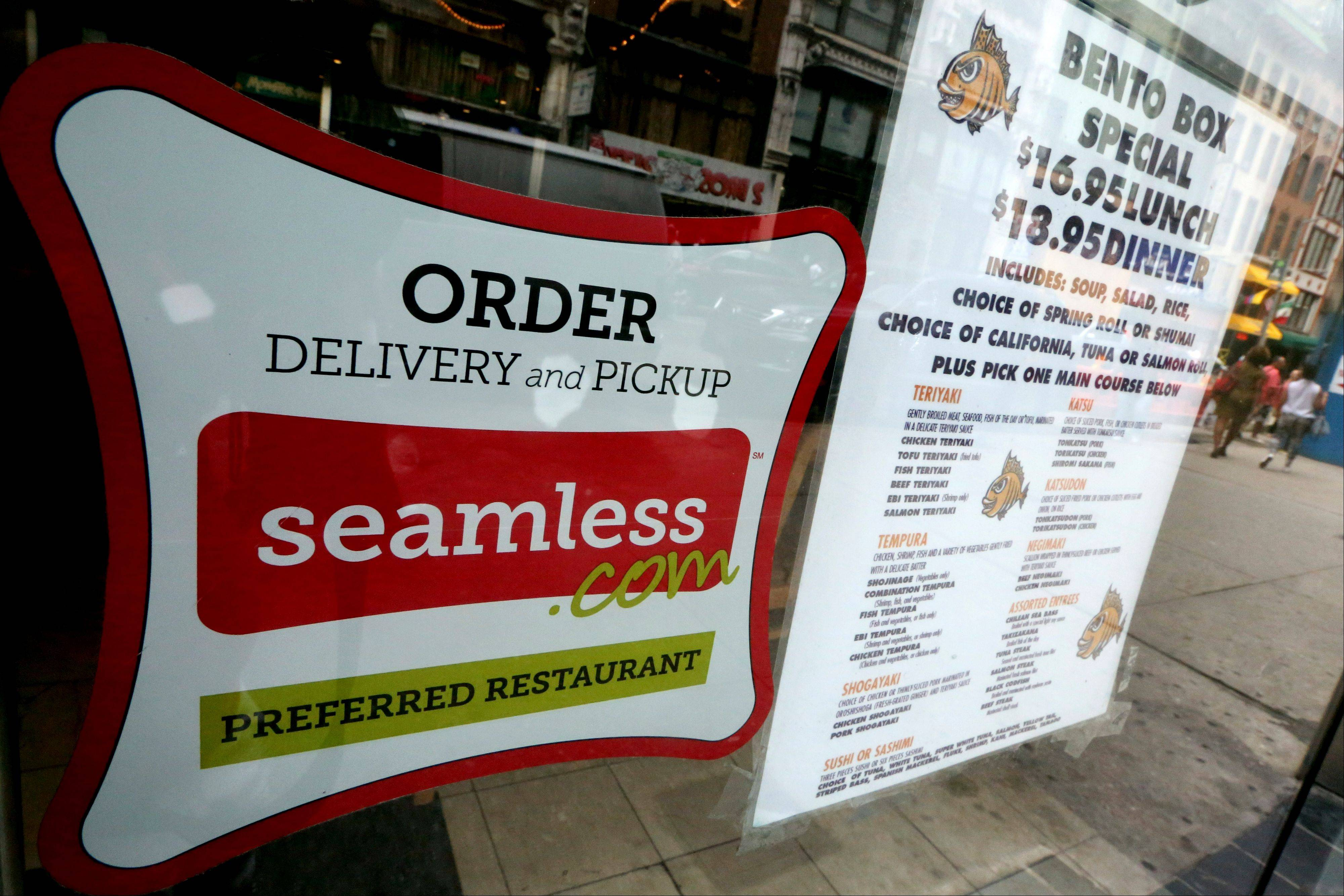 A seamless sticker is displayed next to the menu in the window of a restaurant in New York�s Times Square. Eat24, GrubHub, Seamless, Delivery.com and a growing list of smaller online ordering services have changed the way people order takeout.