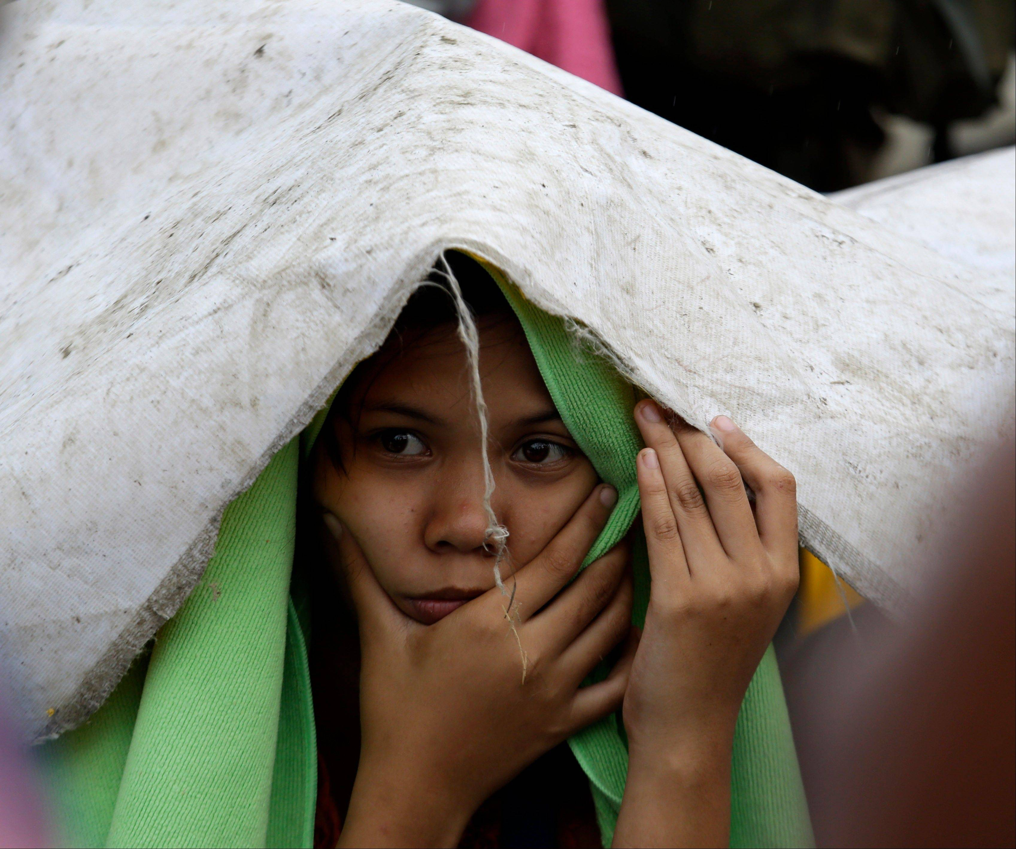 A typhoon survivor waits for a chance to board military transport planes from the U.S., Philippines, Malaysia and Singapore on Sunday at the damaged Tacloban airport, Tacloban city, Leyte province in central Philippines.