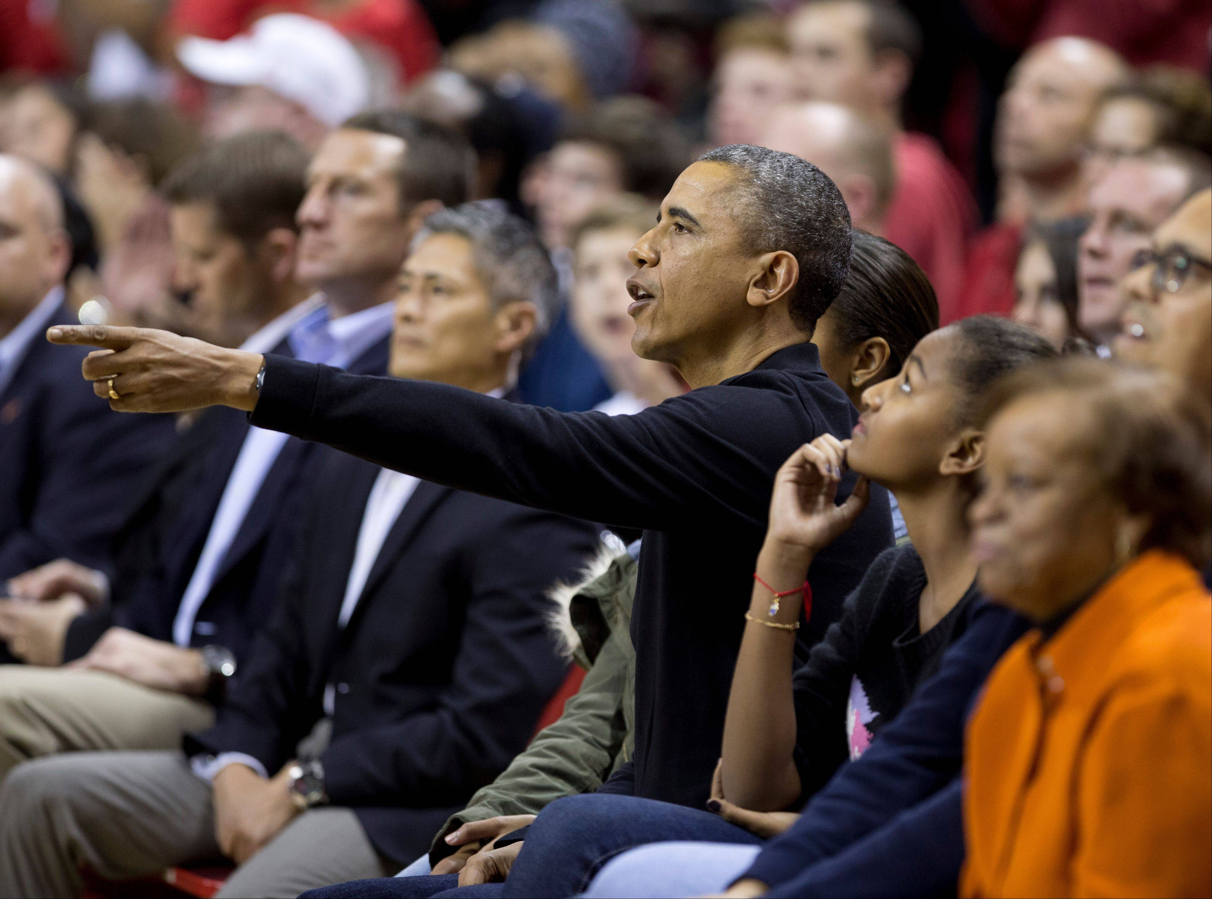 President Barack Obama, third from right, with first lady Michelle Obama, and their daughters Malia, and Sasha, second from left, and mother-in-law Marian Robinson, right, watch a basketball game between his brother-in-law Oregon State Beavers Coach Craig Robinson�s team play against the Maryland Terrapins on Sunday in College Park, Md.