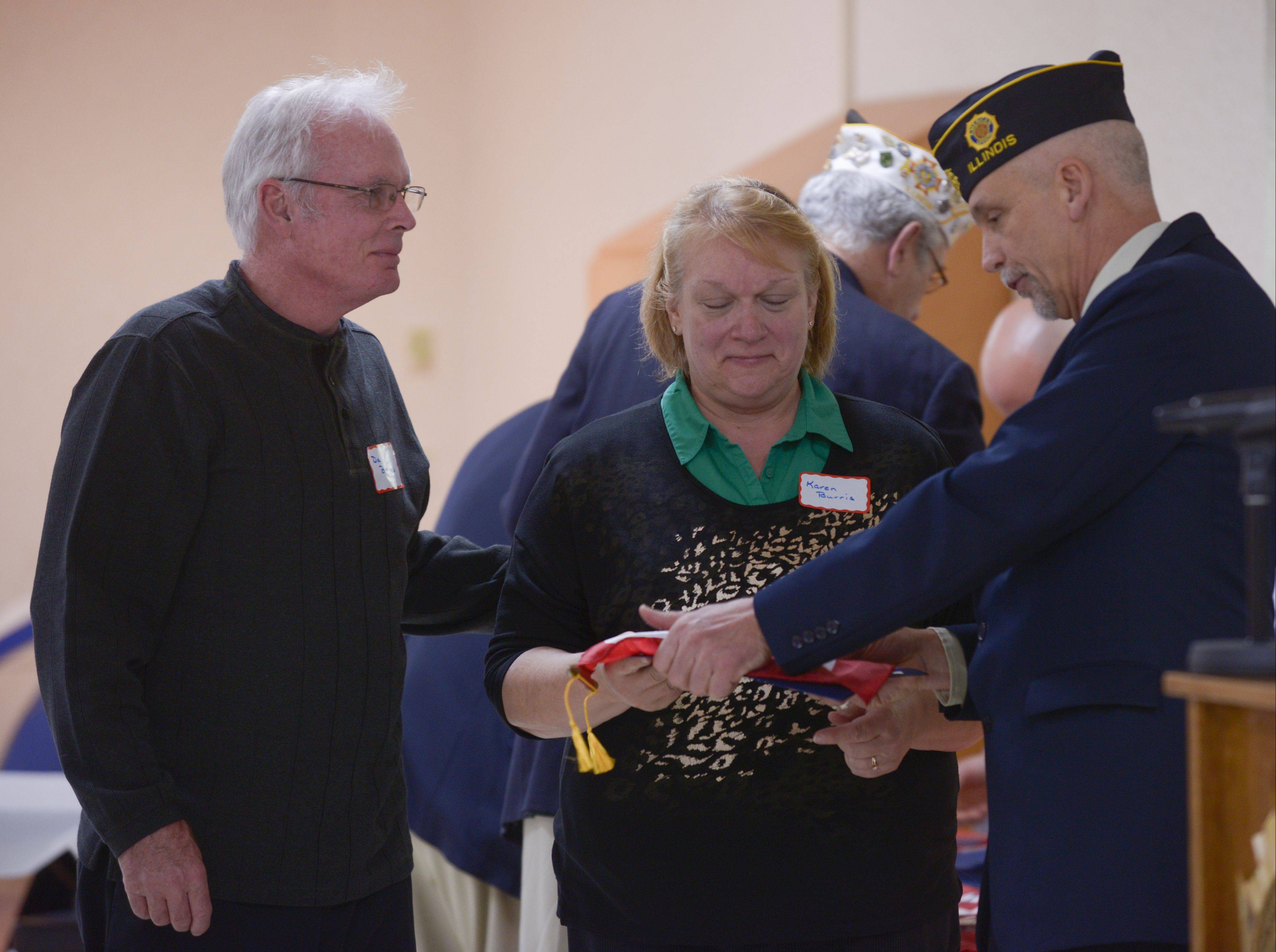 Dan and Karen Burris of Lisle, whose son Ryan is serving in the U.S. Navy, receive a Blue Star Service Banner Sunday at VFW Post 3873 in Naperville from Glenn Granat of American Legion Post 43.