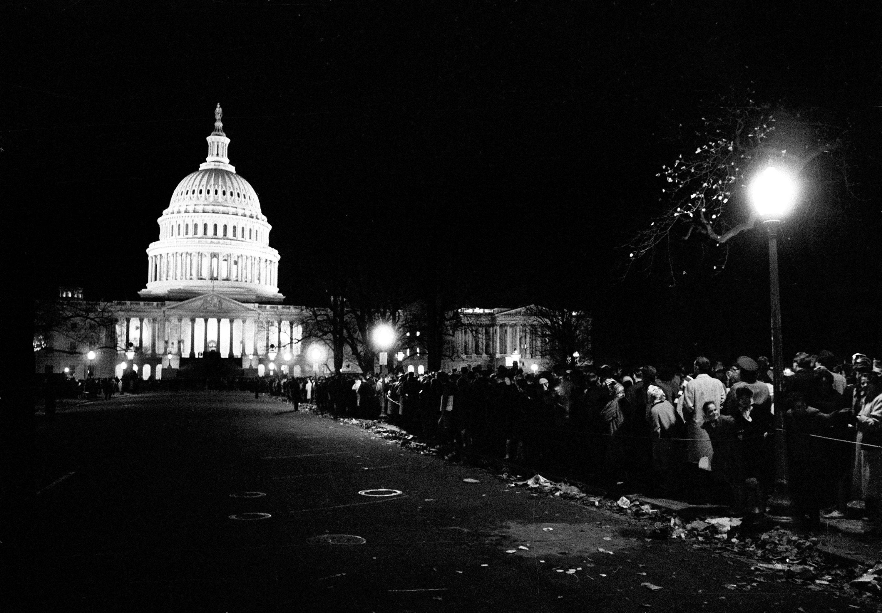 Mourners stand in a line which lasted through the night, to pay their respects to the slain President John F. Kennedy, in Washington, with the illuminated U.S. Capitol in the background.