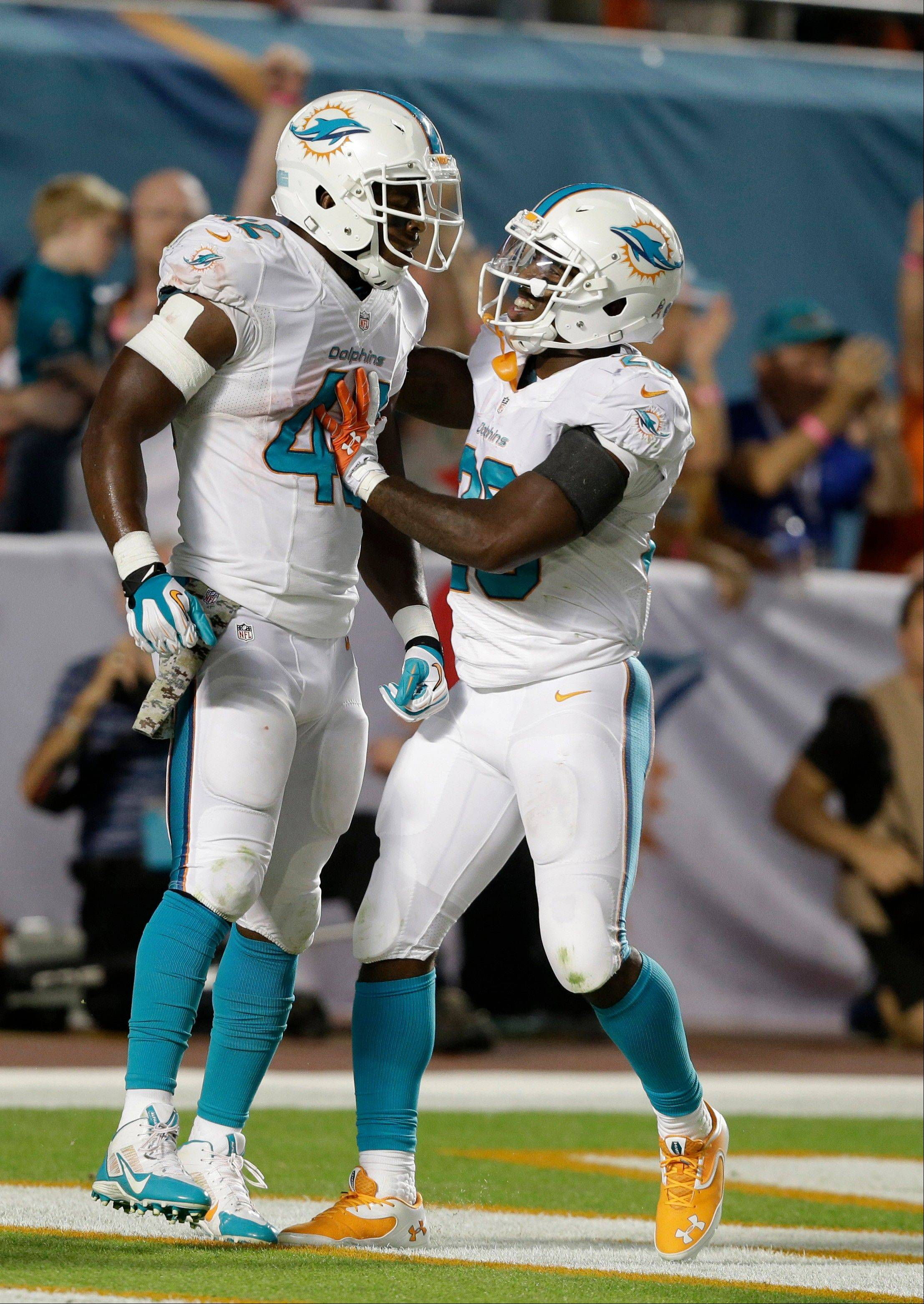 Miami Dolphins tight end Charles Clay (42) is congratulated by running back Lamar Miller (26) after Clay ran 39 yards for a touchdown during the second half of an NFL football game against the San Diego Chargers, Sunday, Nov. 17, 2013, in Miami Gardens, Fla.
