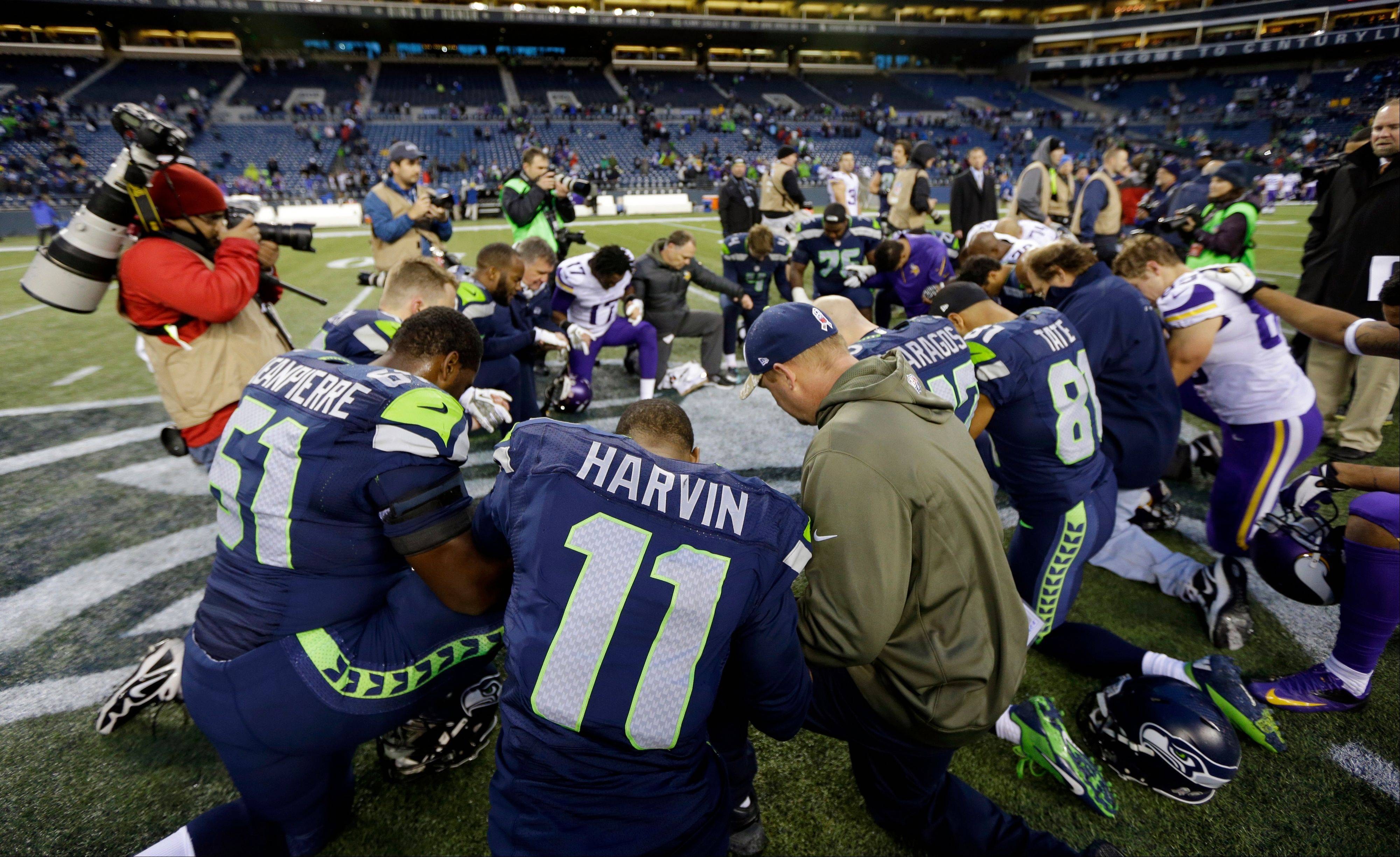 Seattle Seahawks' wide receiver Percy Harvin (11) joins a group of players in kneeling on the field after the Seahawks beat the Minnesota Vikings 41-20 in an NFL football game, Sunday, Nov. 17, 2013, in Seattle.