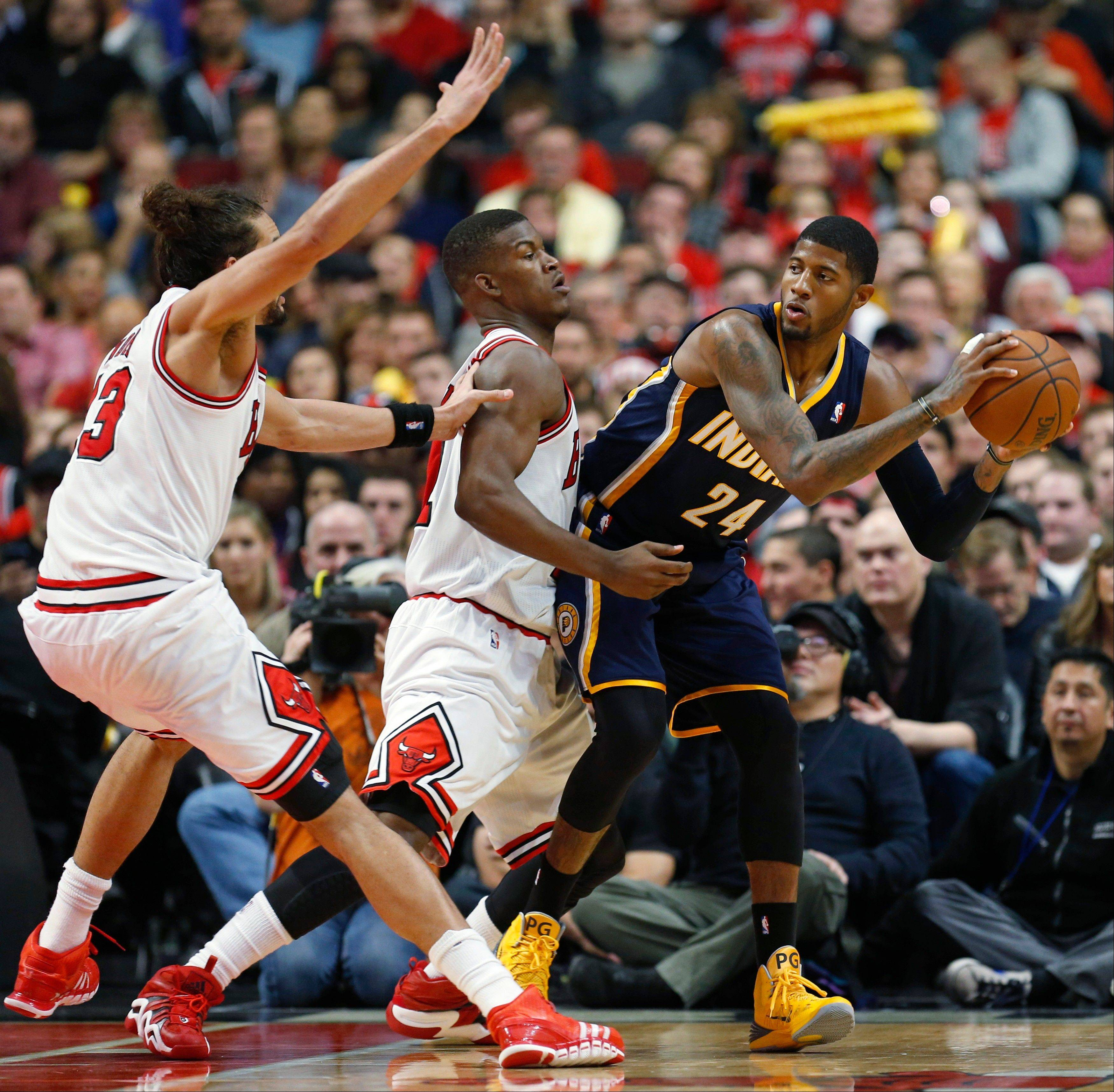 Pacers forward Paul George is defended by Bulls guard Jimmy Butler, middle, and center Joakim Noah during Saturday�s Bulls victory. It would benefit either of these teams to get the No. 1 seed in the East.