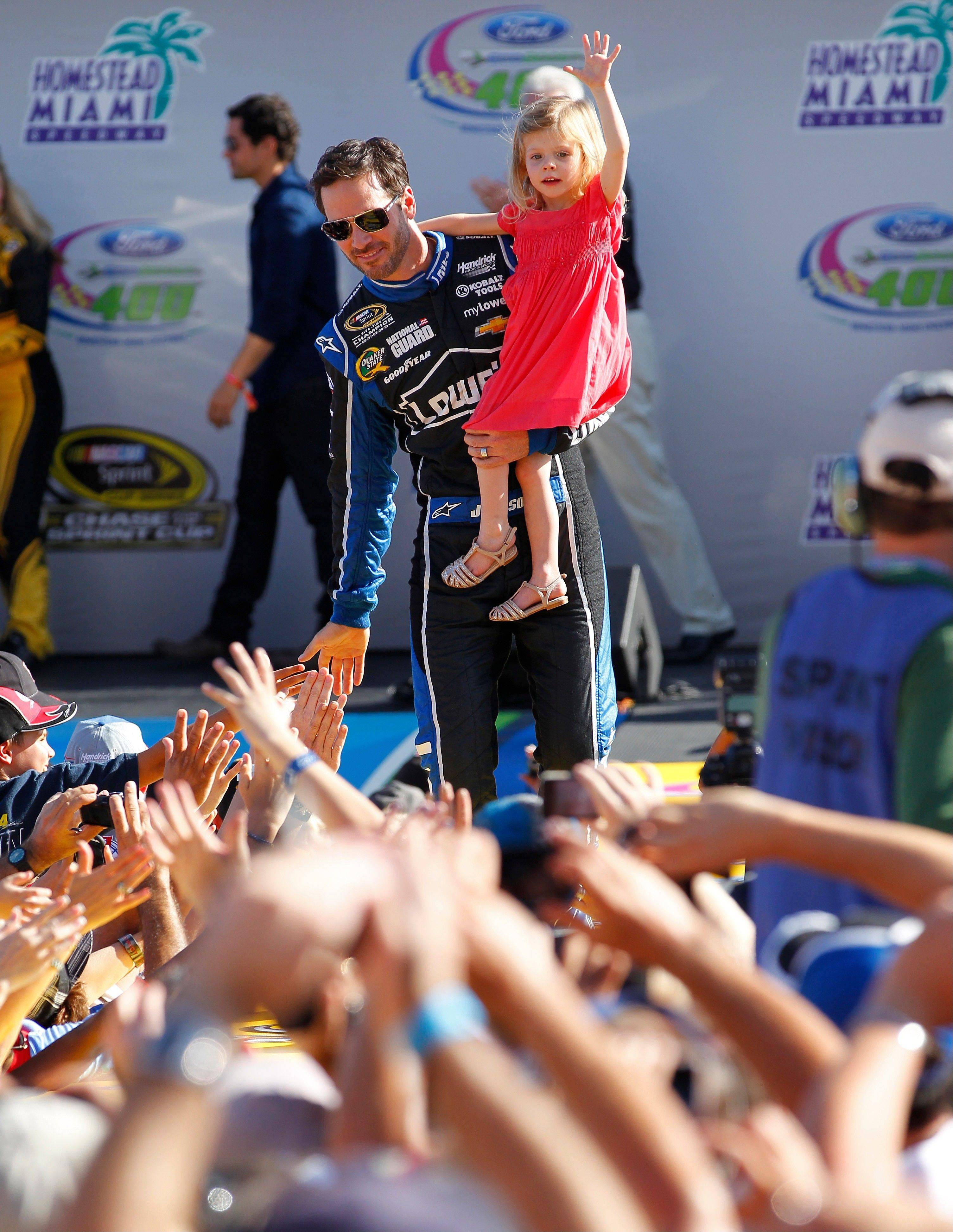 Jimmie Johnson with his daughter, Genevieve, greet fans during driver introductions before the NASCAR Sprint Cub Series auto race in Homestead, Fla., Sunday, Nov. 17, 2013.