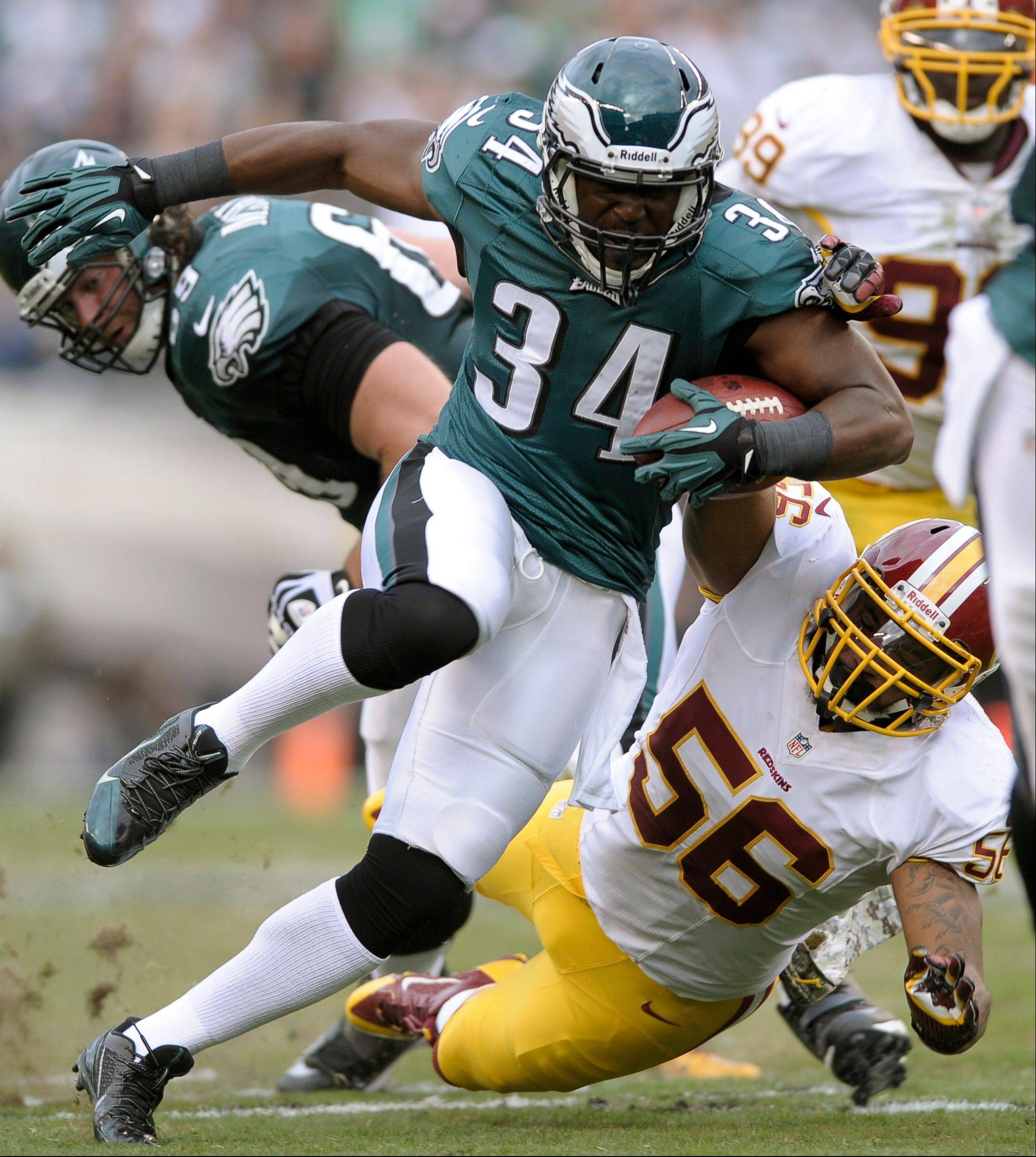 Philadelphia Eagles running back Bryce Brown (34) escapes the grasp of Washington linebacker Perry Riley during the first half of an NFL football game in Philadelphia, Sunday, Nov. 17, 2013.