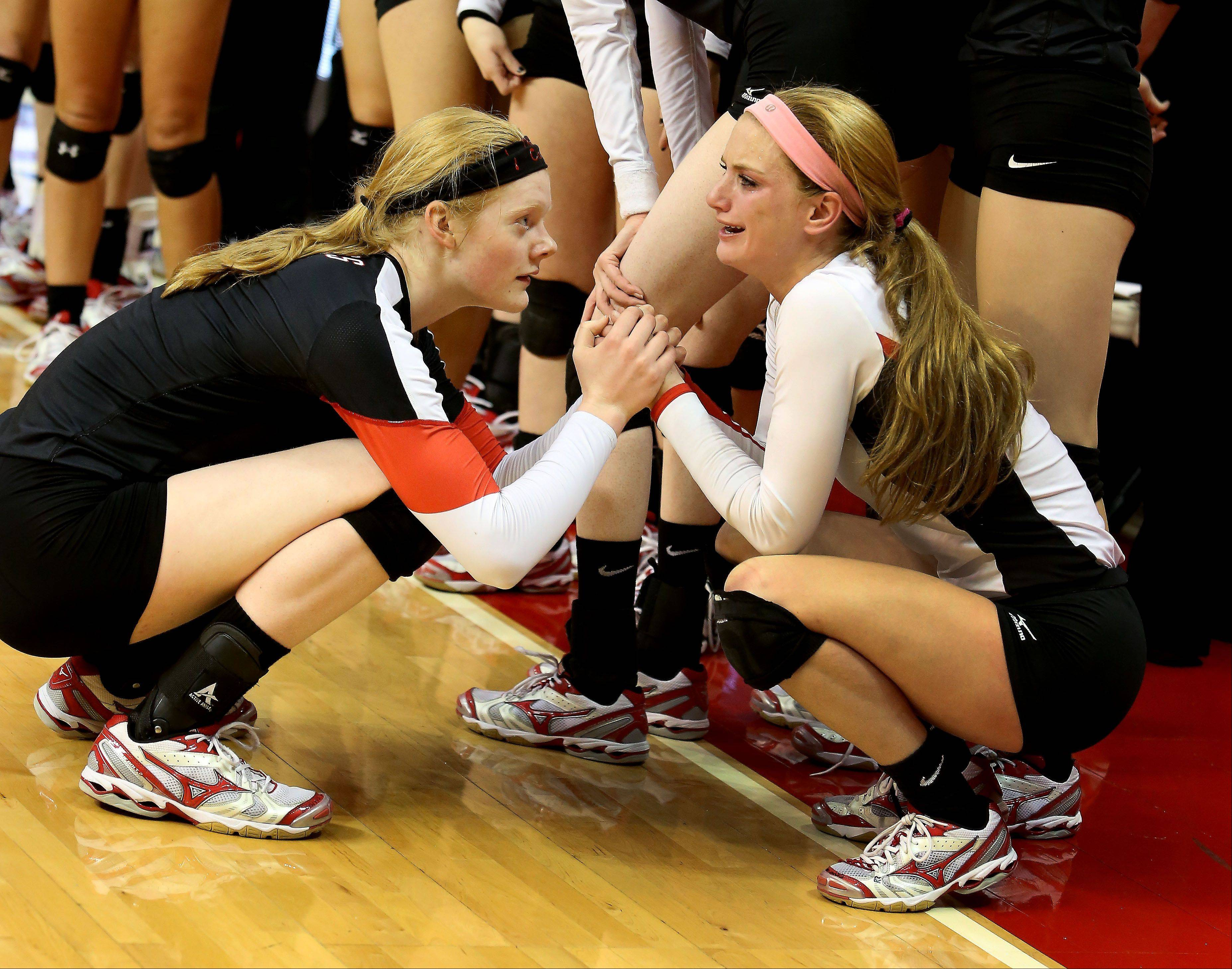 Rachael Fara, left and Caroline Wolf, right, of Benet console each other after their loss to Mother McAuley in the Class 4A championship girls volleyball match on Saturday in Normal.
