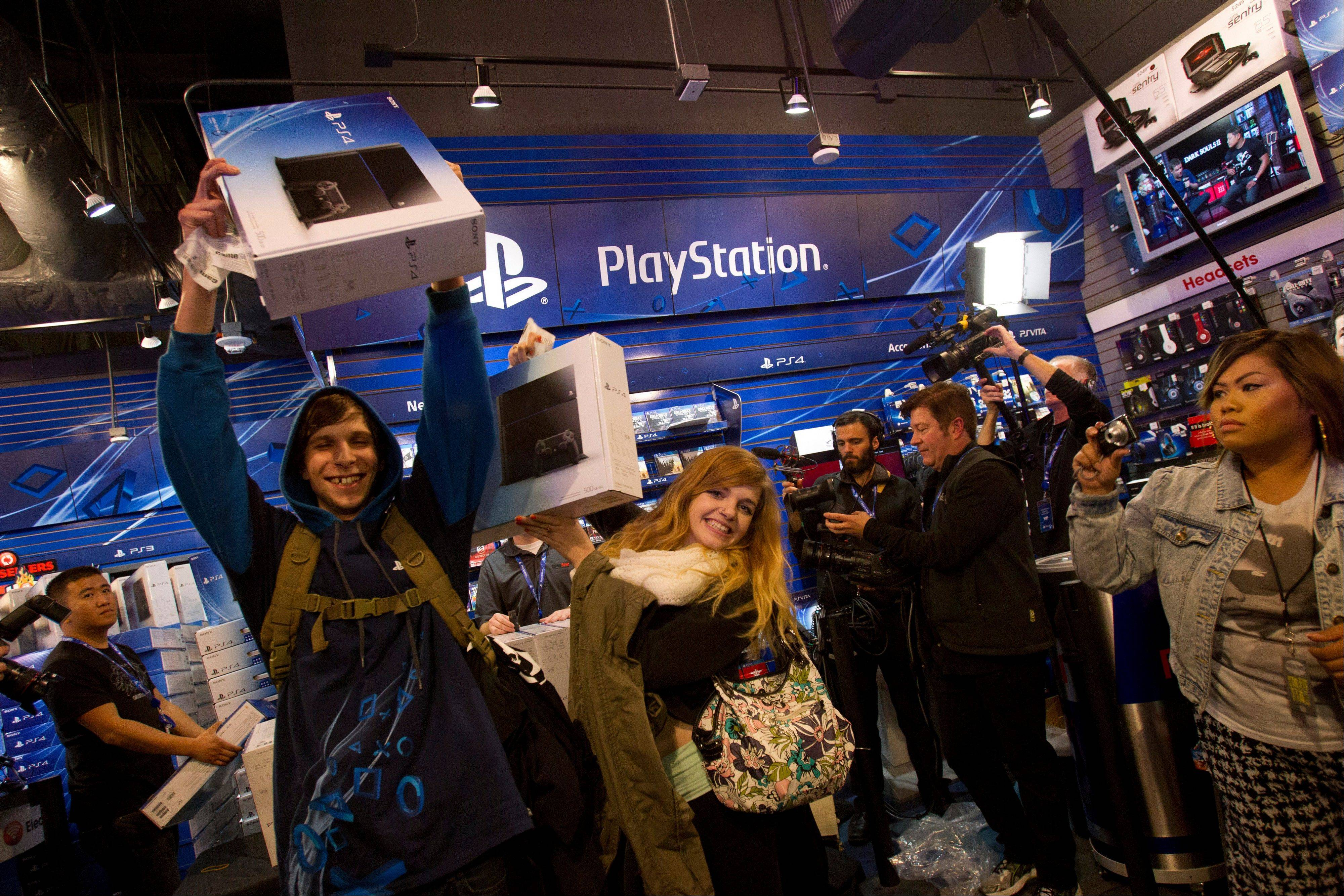 Brenden Hartnet, left, and Sydnee Mencuri, center, celebrate after purchasing the Sony PlayStation 4 console during its midnight launch event in San Francisco on Thursday.