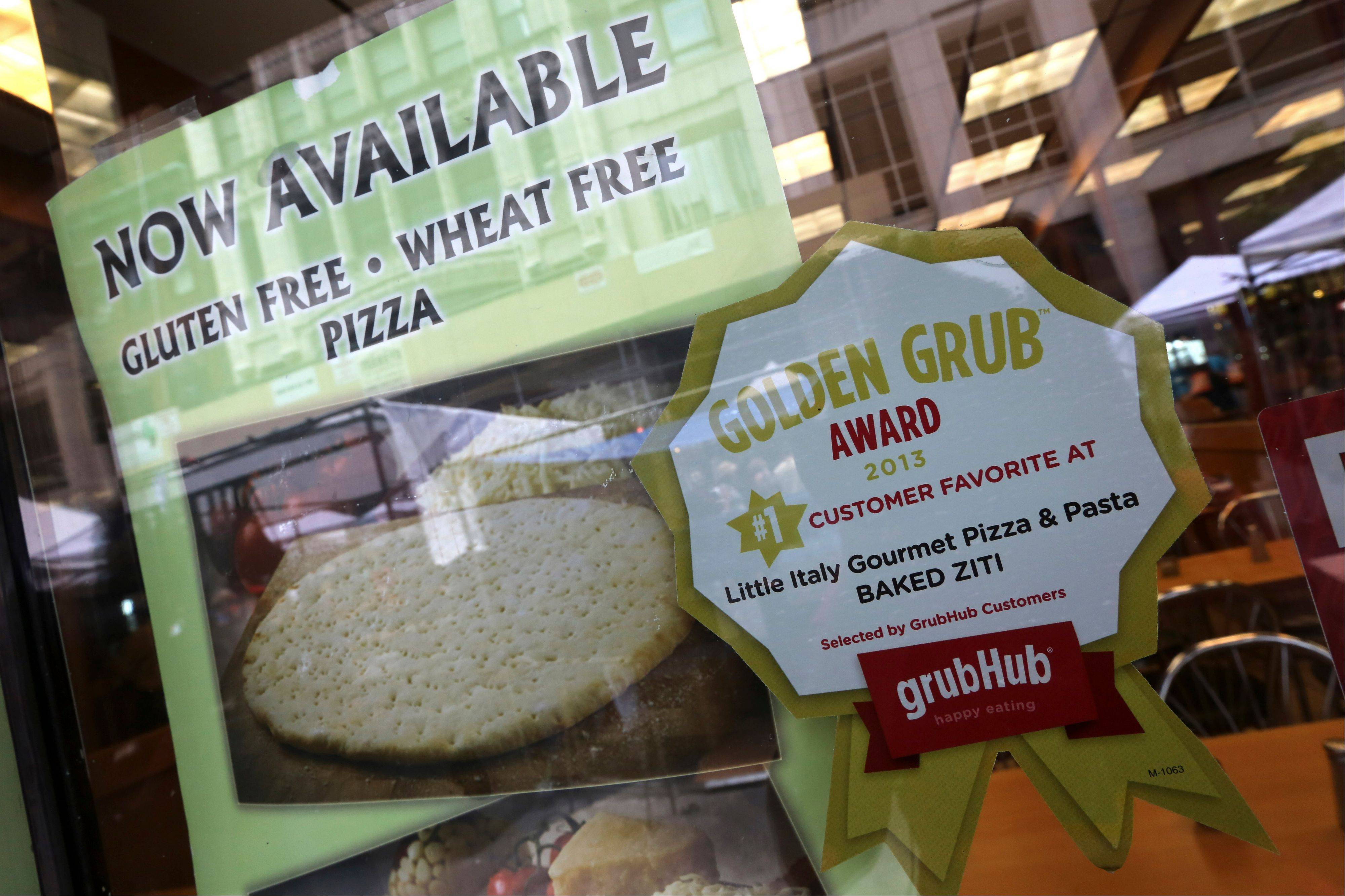 A GrubHub sticker is displayed next to photographs of items on the menu in the window of a restaurant in New York's Times Square.