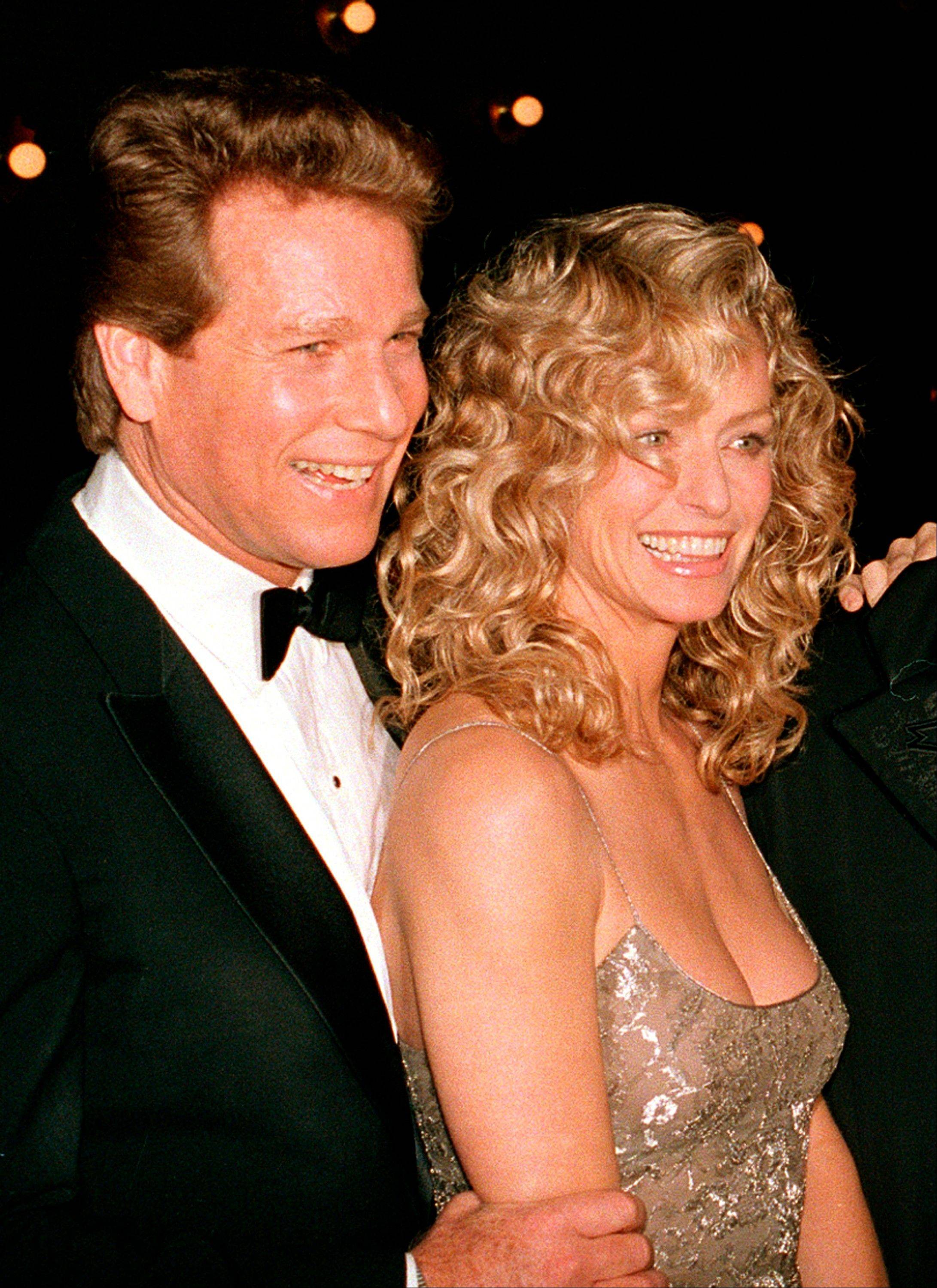 "This March 5, 1989 file photo shows actors Ryan O'Neal, left, and Farrah Fawcett at the premiere of the film. ""Chances Are,"" in New York. Jury selection could begin as early as Thursday, Nov. 21, in a Los Angeles courtroom in a dispute between O'Neal and the University of Texas at Austin over the ownership of an Andy Warhol portrait of Fawcett."
