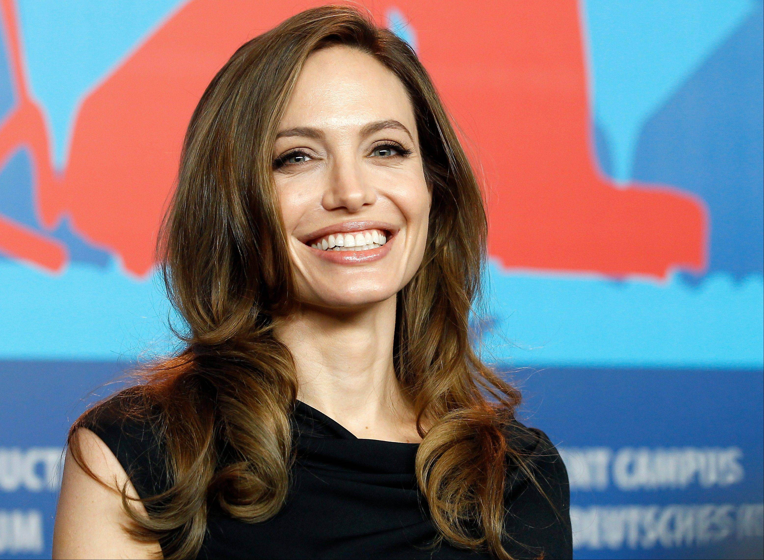 "In this Feb. 11, 2011 file photo, Director Angelina Jolie smiles during the press conference of the film ""In the Land of Blood and Honey,"" at the 62 edition of the Berlinale, International Film Festival in Berlin. The Board of Governors of the Academy of Motion Picture Arts and Sciences will present Honorary Awards to Angela Lansbury, Steve Martin and Piero Tosi, and the Jean Hersholt Humanitarian Award to Jolie. All four awards will be presented at the Academy's 5th Annual Governors Awards on Saturday, November 16, 2013, at the Ray Dolby Ballroom at the Hollywood & Highland Center in the Hollywood section of Los Angeles."