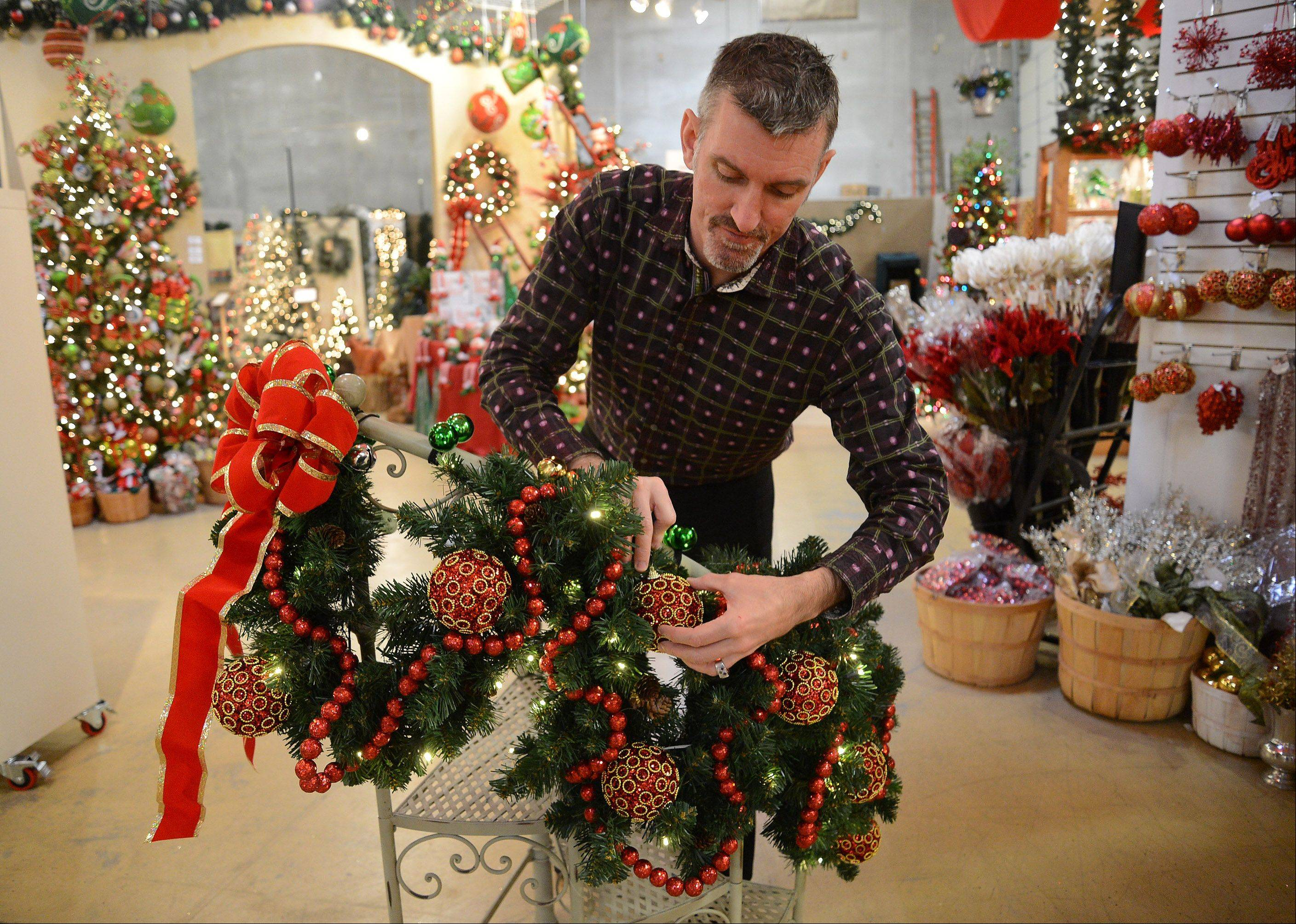 Designer James Whitehead of Treetime Christmas Creations in Lake Barrington puts together a display of garland with battery-operated lights on a railing.