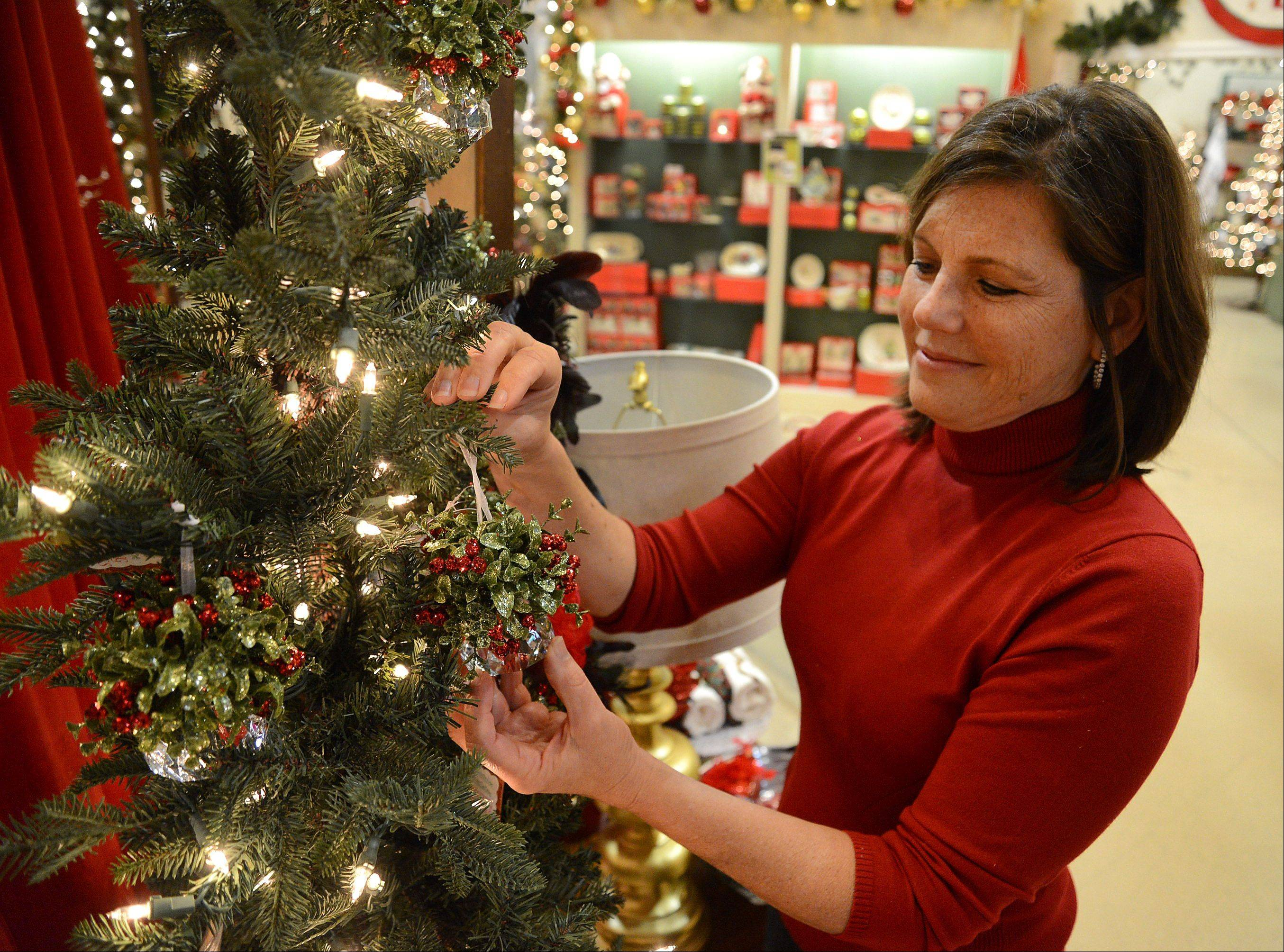 Owner Laurie Kane of Treetime Christmas Creations in Lake Barrington, attaches kissing crystals on a tree.