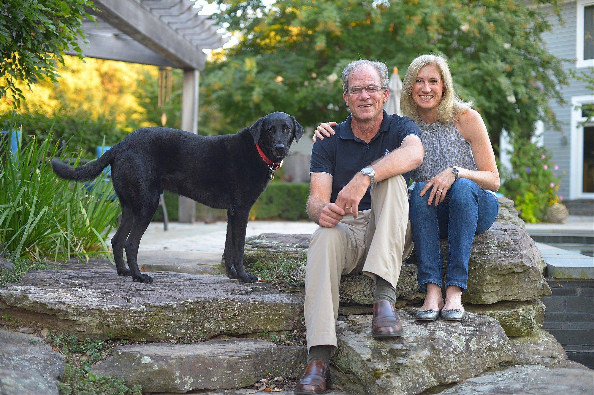 Owners Josh and Jill Baker, with their dog, Auggie, sit near their backyard pool and patio in Great Falls, Va.