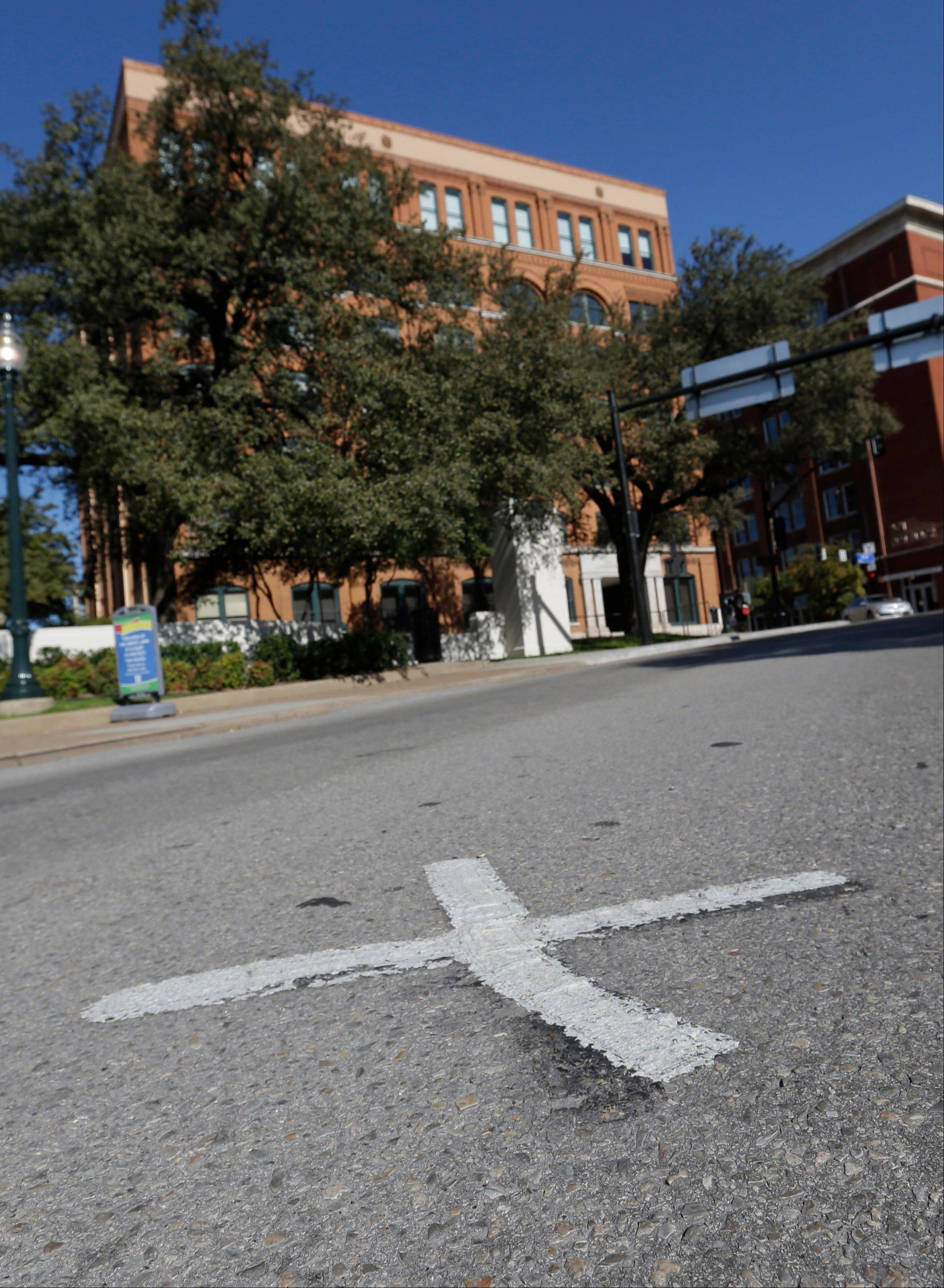 An X marks the spot on Elm Street where the first bullet hit President John F. Kennedy on Nov. 22, 1963, near the former Texas School Book Depository, now known as the Sixth Floor Museum, background, on Dealey Plaza in Dallas.